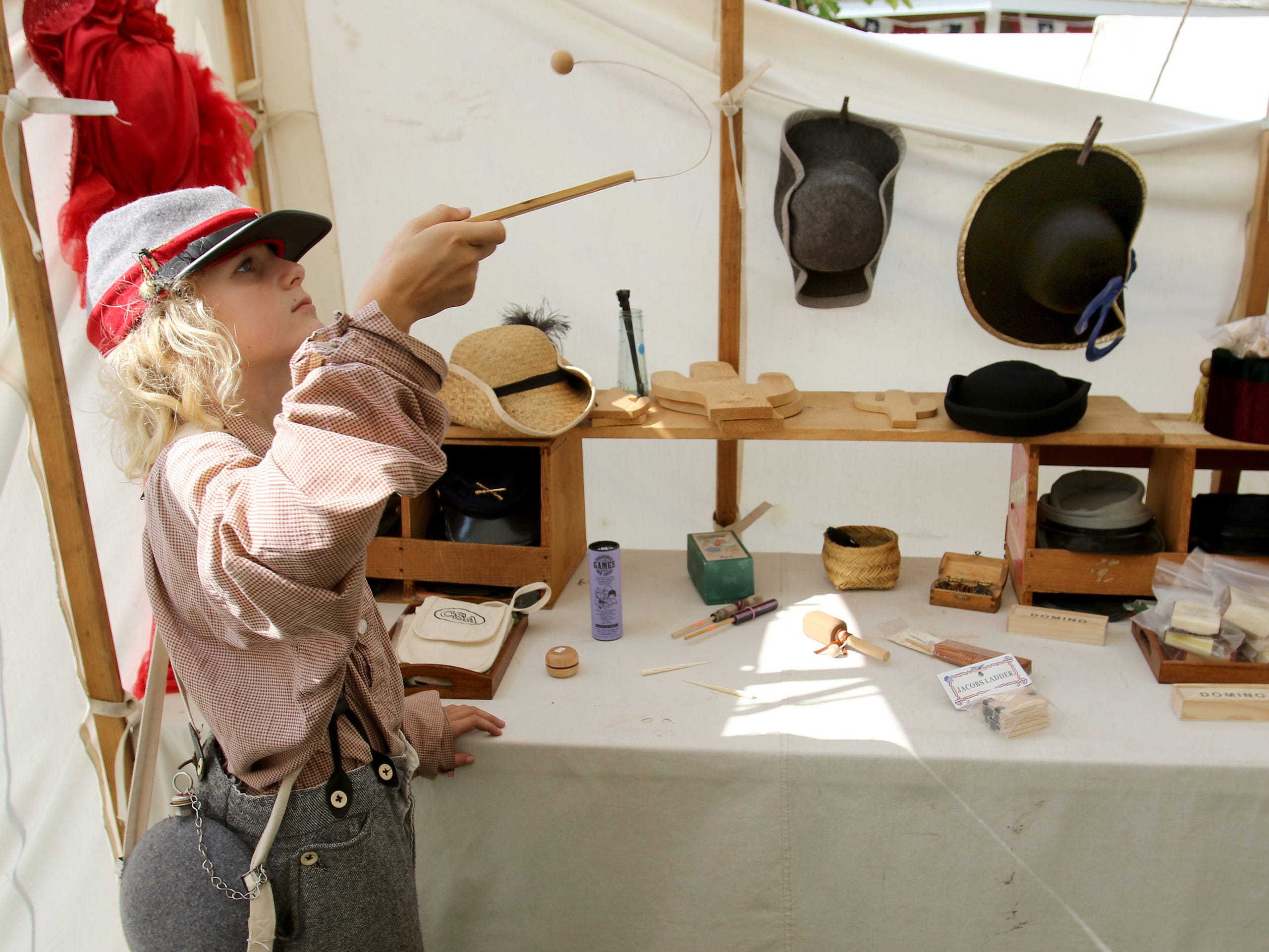 Lucas Vater of Fox Point tries a vintage toy in a store offering period items during Settler's Weekend at the West Allis Historical Society Grounds on Aug. 25.