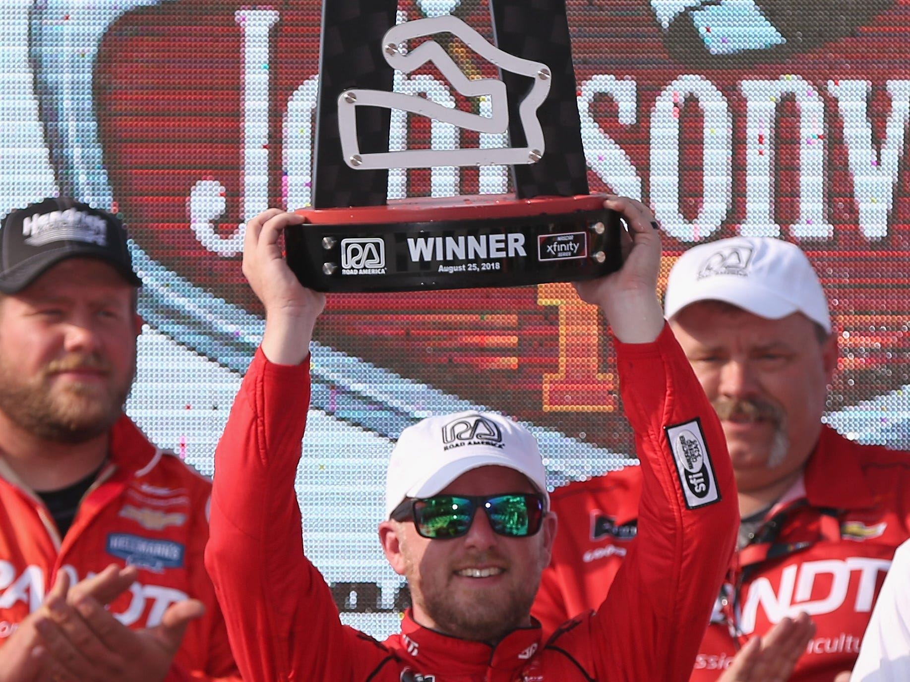 Justin Allgaier hoists the trophy for winning the NASCAR Xfinity Series Johnsonville 180 on Saturday at Road America in Elkhart Lake.