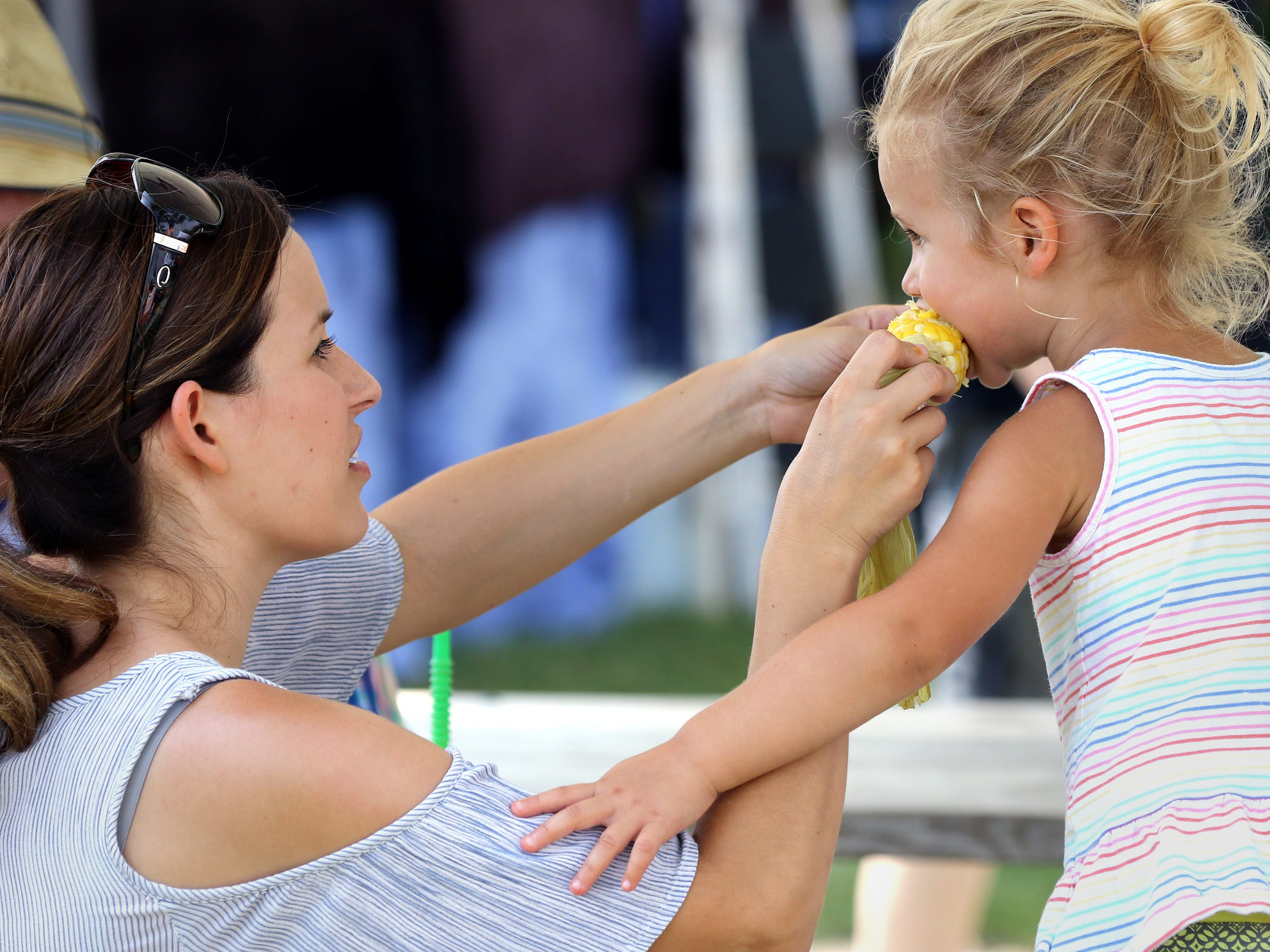 Katie (left) and Emma Ferch of Cedarburg share an ear of roasted corn during the Muskego Community Festival at Muskego Veterans Memorial Park on Aug. 25.