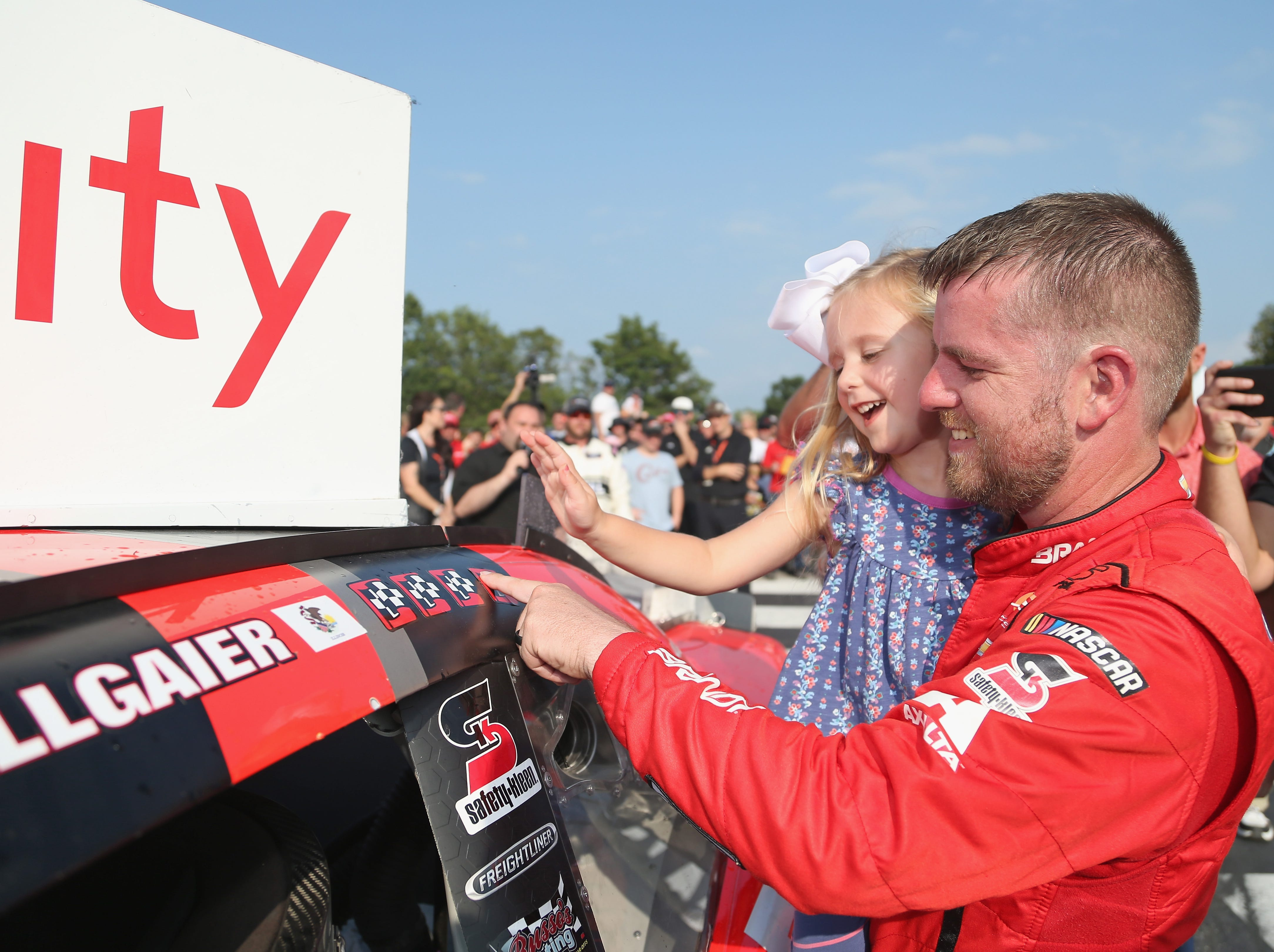ELKHART LAKE, WI - AUGUST 25:  Justin Allgaier, driver of the #7 BRANDT Professional Agriculture Chevrolet, applies with winner's sticker with his daughter, Harper, after winning the NASCAR Xfinity Series Johnsonville 180 at Road America on August 24, 2018 in Elkhart Lake, Wisconsin.  (Photo by Matt Sullivan/Getty Images)