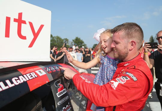 Justin Allgaier and his daughter, Harper, apply the decal signifying his fourth victory of the season.