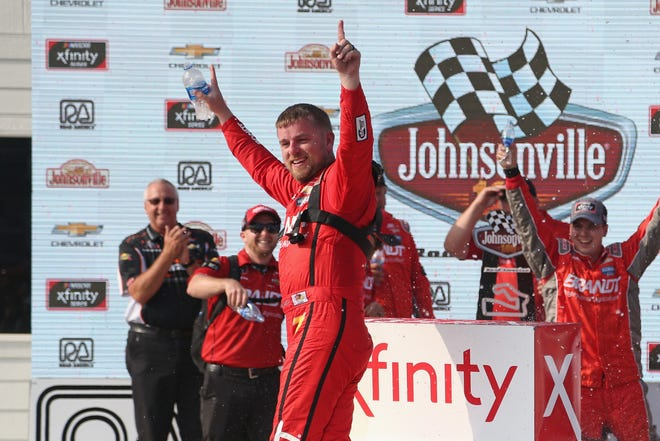 Justin Allgaier climbs out of his car in victory lane Saturday after becoming the ninth consecutive different Xfinity Series winner at Road America.