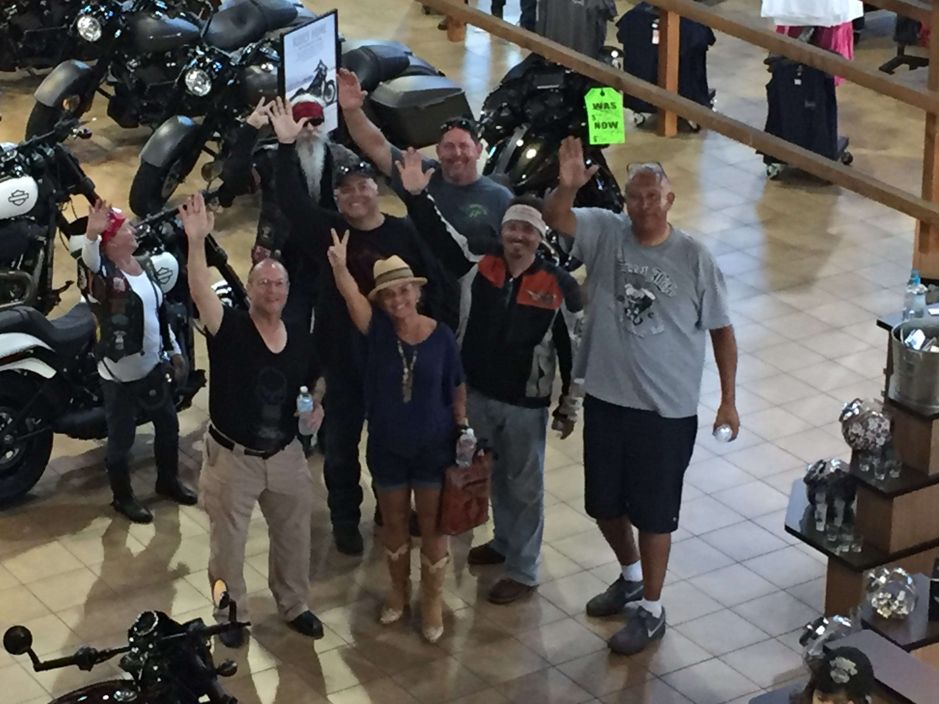 Riders from the San Diego to Milwaukee ride wave from the floor of Harley-Davidson World in Oklahoma City, which hosted about 150 people at a welcome party on Aug. 24, leg 4 of the nine-day trip to Milwaukee.