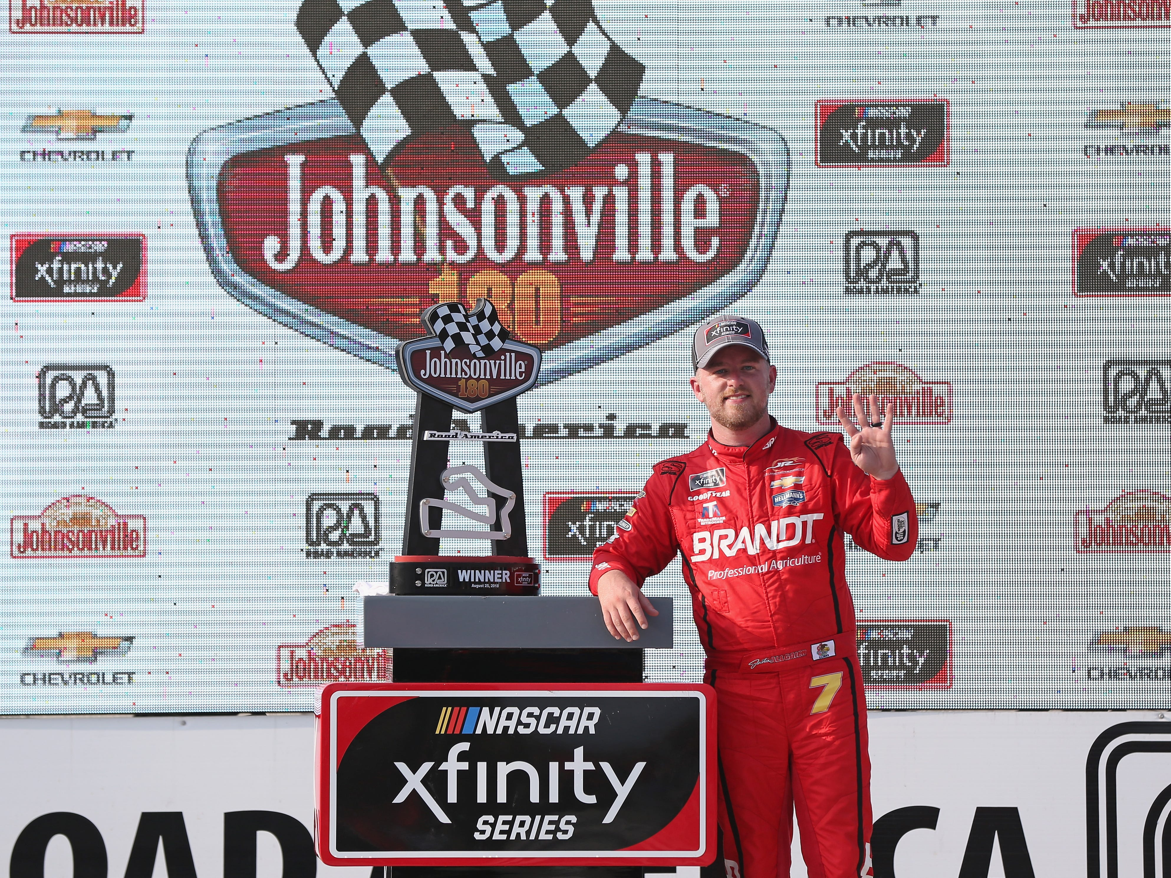 Justin Allgaier stands next to the trophy for winning the Johnsonville 180 on Saturday.