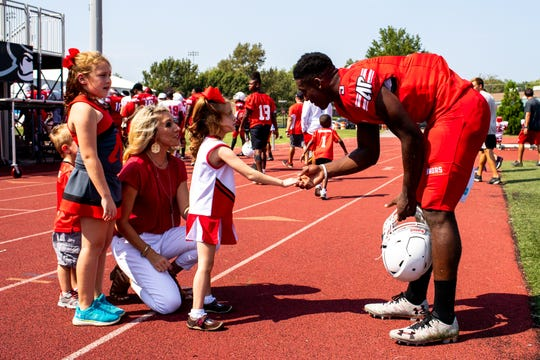 Austin Peay Quarterback Javaughn Craig says hello to Landrey Eargle, 5, before heading inside during a scrimmage at Fortera Stadium Saturday, Aug. 25, 2018, in Clarksville, Tenn. Landrey has a rare gene mutation that threatens her life and causes epilepsy, intellectual disability, immunodeficiency and cardiac problems. Landrey's father Joshua Eargle is Austin Peay State University's offensive line coach.