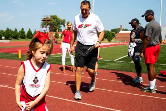 Joshua Eargle follows his daughter Landrey, 5, during a scrimmage at Fortera Stadium Saturday, Aug. 25, 2018, in Clarksville, Tenn. Landrey has a rare gene mutation that threatens her life and causes epilepsy, intellectual disability, immunodeficiency and cardiac problems. Joshua Eargle is Austin Peay State University's offensive line coach.