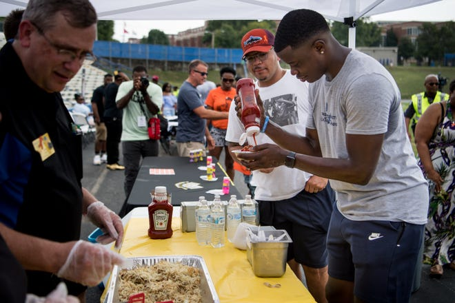 "Waffle House shooting survivors James Shaw Jr., right, and Brennan ""BJ"" McMurry, center, put toppings on some Waffle House hash browns during the first Come Together Day at Tennessee State University, Sunday, Aug. 26, 2018, in Nashville, Tenn. This was their first time eating Waffle House food since the deadly shooting at a restaurant in Antioch."