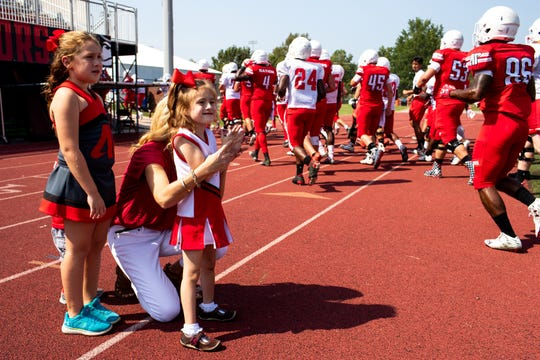 Landrey Eargle, 5, stands with her mother and sister Kristen and Kourtney, 7, as they applaud for the Austin Peay players as they head inside during a scrimmage at Fortera Stadium Saturday, Aug. 25, 2018, in Clarksville, Tenn. Landrey has a rare gene mutation that threatens her life and causes epilepsy, intellectual disability, immunodeficiency and cardiac problems. Landrey's father Joshua Eargle is Austin Peay State University's offensive line coach.