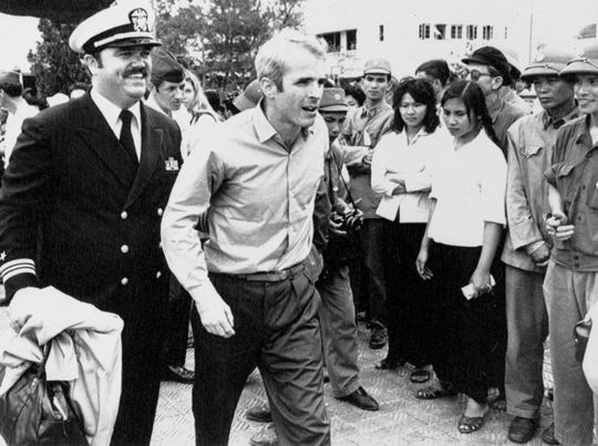 Navy Lt. Cmdr. John McCain, center, is escorted March 14, 1973, by Lt. Cmdr. Jay Coupe Jr. to Hanoi, Vietnam's Gia Lam Airport, after McCain was released from captivity.