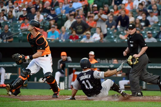 Aug 25, 2018; Baltimore, MD, USA; New York Yankees left fielder Brett Gardner (11) slides past Baltimore Orioles catcher Caleb Joseph (36) to score during the first inning at Oriole Park at Camden Yards.