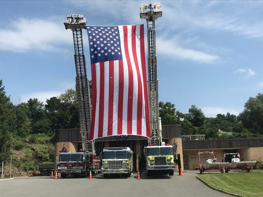 An American flag was held outside  P.O.L. Fire Company 2 in Wayne on Sunday in honor of former volunteer firefighter Adam Jobbers-Miller