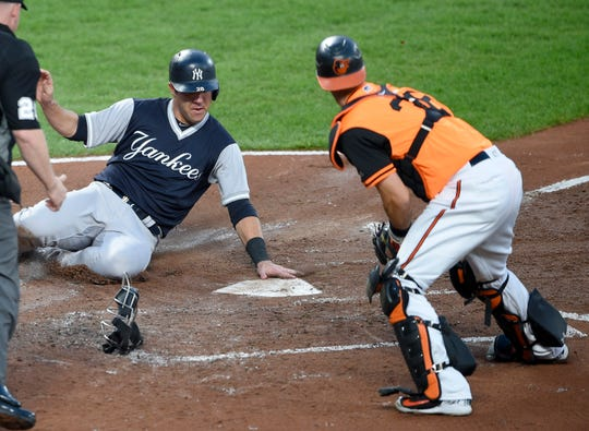 New York Yankees' Austin Romine, left, slides home to score against Baltimore Orioles catcher Caleb Joseph, right, during the second inning of the second baseball game of a split doubleheader, Saturday, Aug. 25, 2018, in Baltimore.