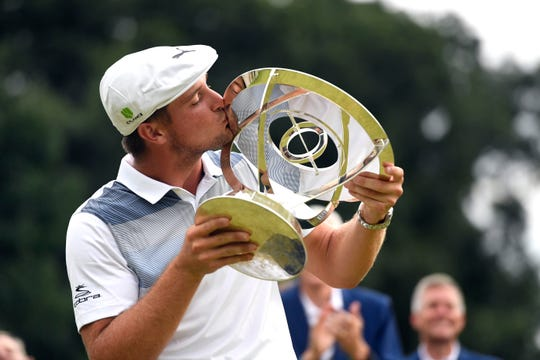 Bryson DeChambeau kisses the Northern Trust trophy during the presentation on the 18th green at the Ridgewood Country Club in Paramus, NJ on Sunday, August 26, 2018.