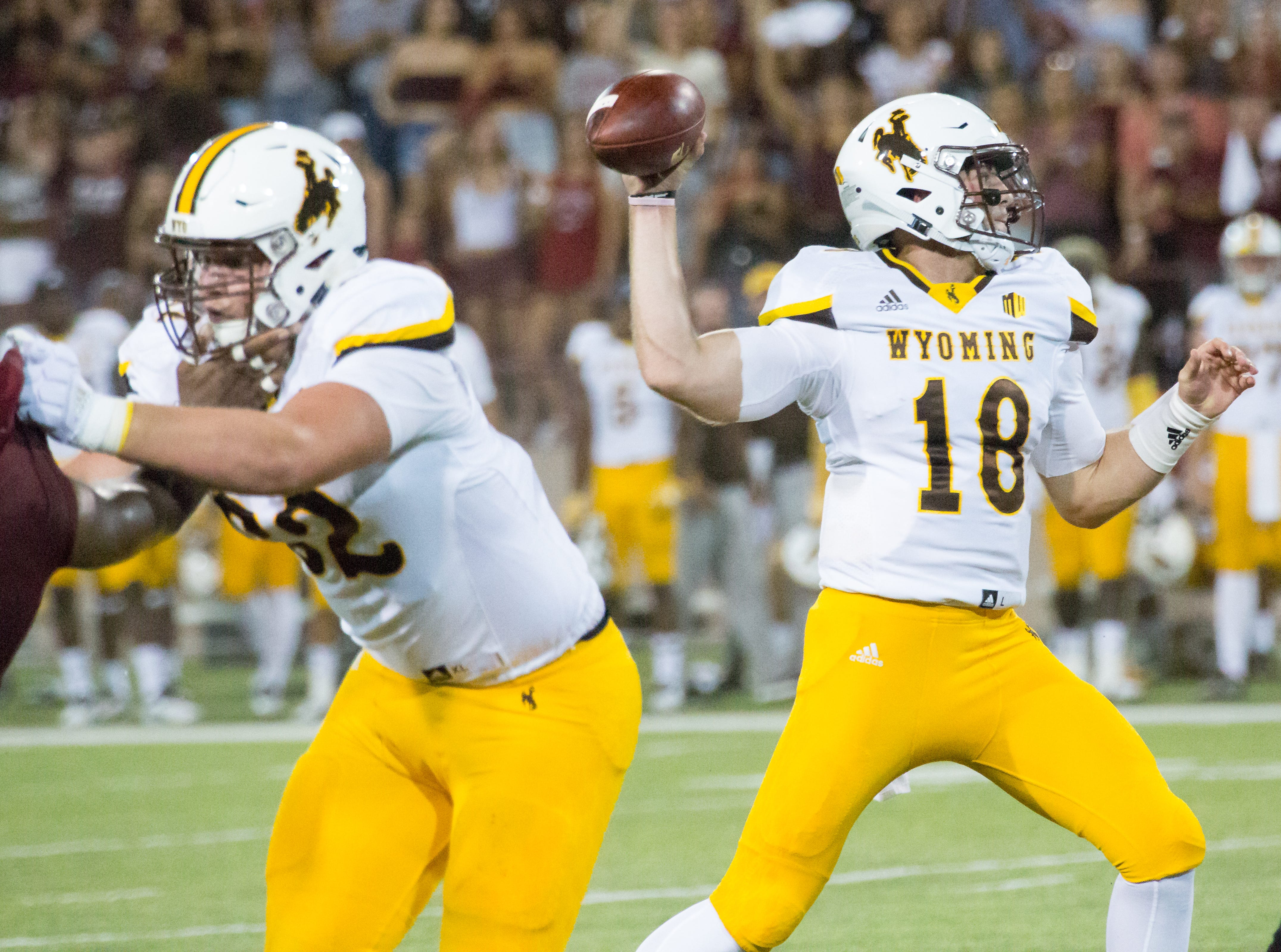 Wyoming quarterback Tyler Vander Waal looks to connect with a receiver as an New Mexico State University defender tracks him in the forground on Saturday, August 25, 2018, during the NMSU/Wyoming game at the Aggie Memorial Stadium.