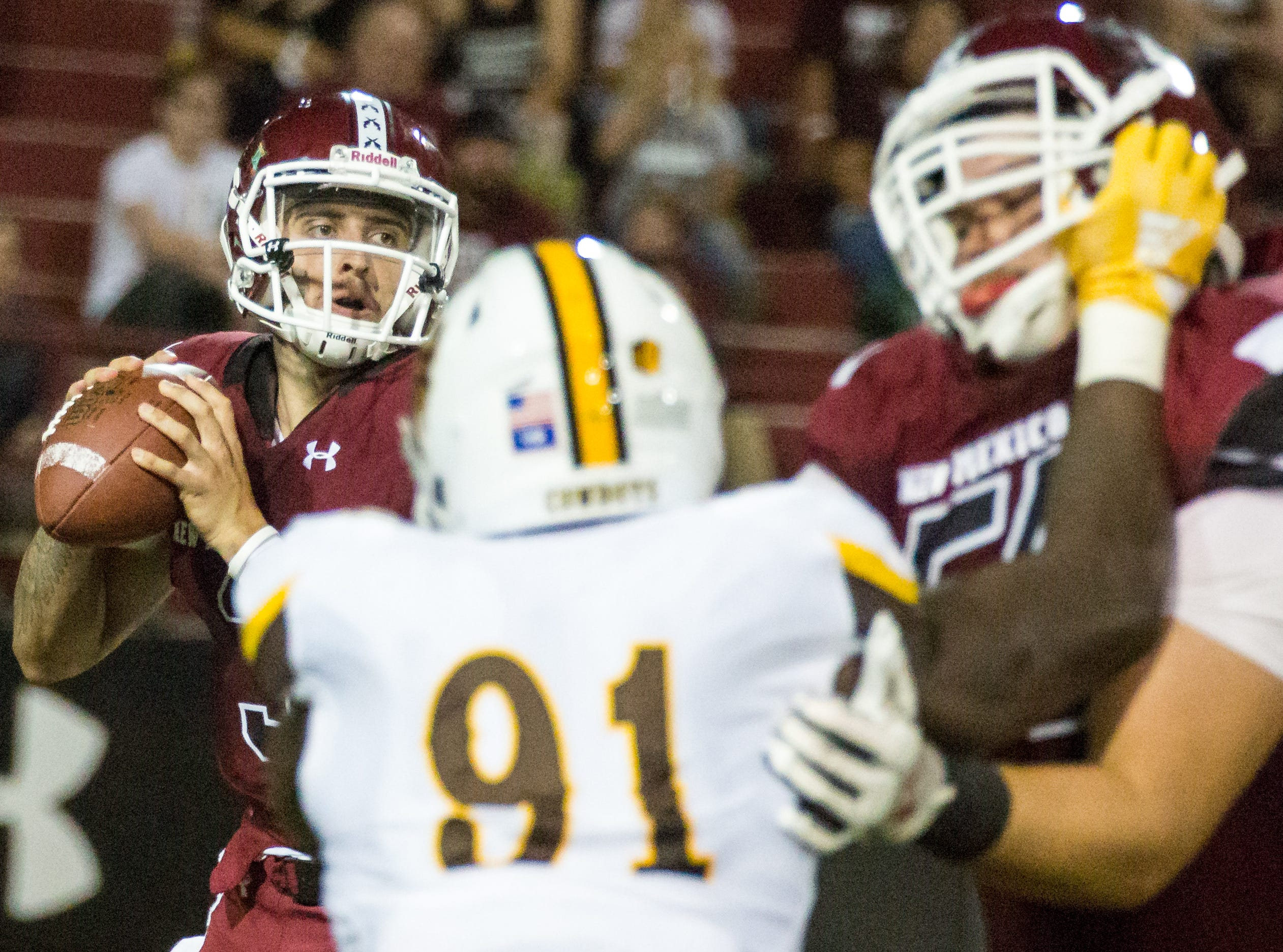NMSU quarterback Matt Romero looks for a receiver with traffic in the foreground on Saturday, August 25, 2018, during the NMSU/Wyoming game at the Aggie Memorial Stadium.