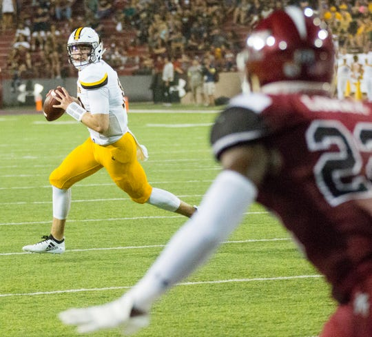 Wyoming quarterback Tyler Vander Waal looks for a receiver as an New Mexico State University defender tracks him in the forground on Saturday, August 25, 2018, during the NMSU/Wyoming game at the Aggie Memorial Stadium.