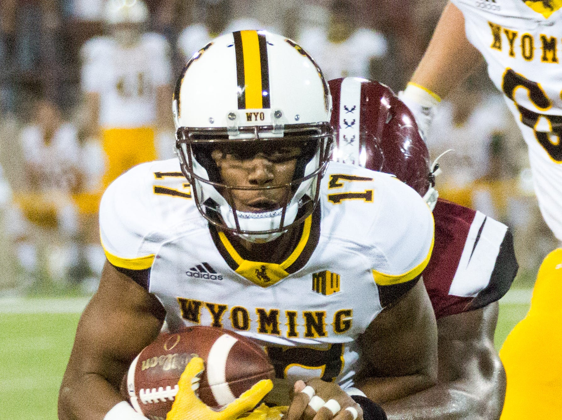 Wyoming's Raghib Ismail Jr. runs for yards while being wrapped up by an NMSU defender on Saturday, August 25, 2018, during the NMSU/Wyoming game at the Aggie Memorial Stadium.