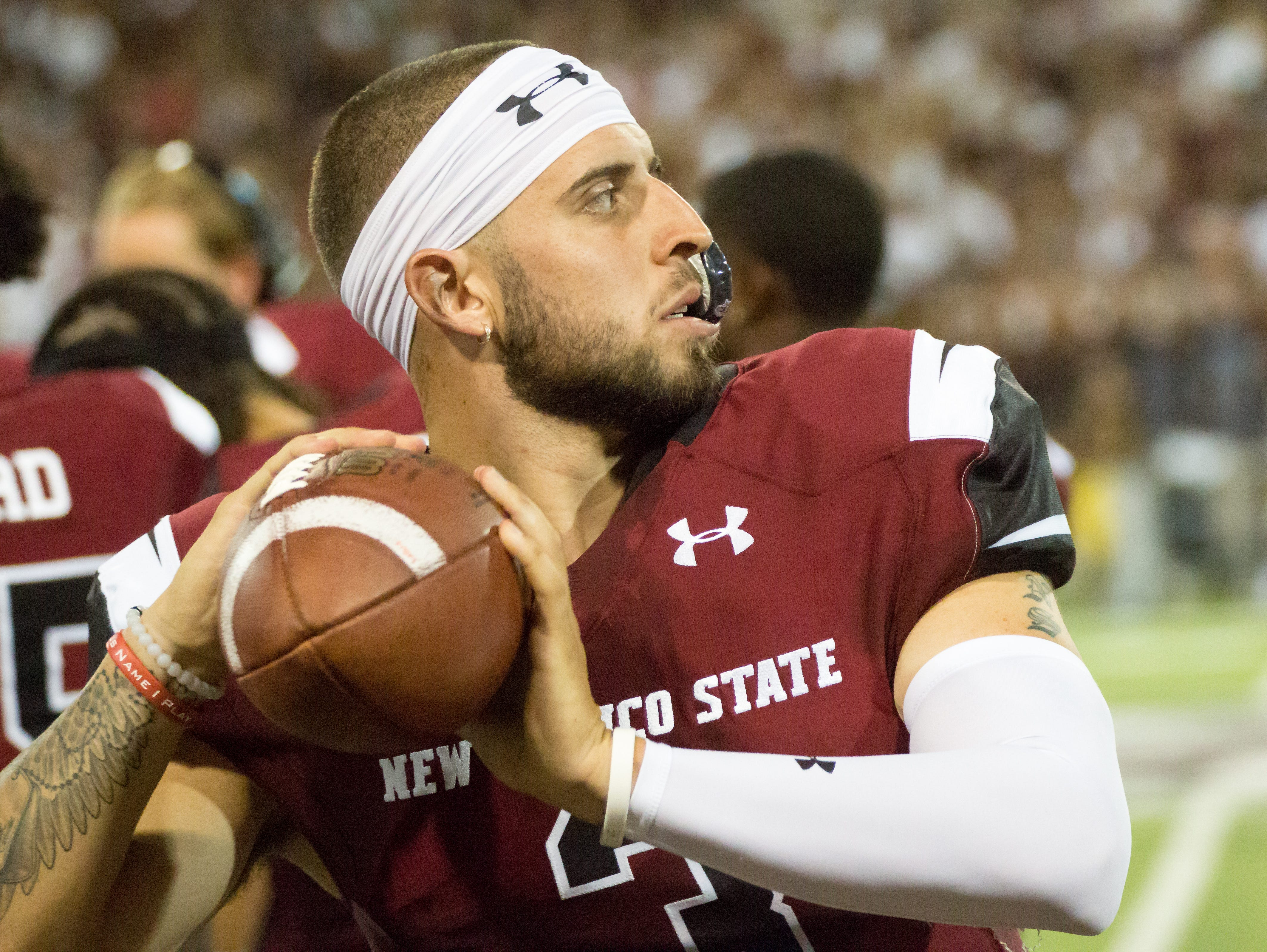 NMSU quarterback Matt Romero warms up on the sidelines on Saturday, August 25, 2018, during the NMSU/Wyoming game at the Aggie Memorial Stadium.