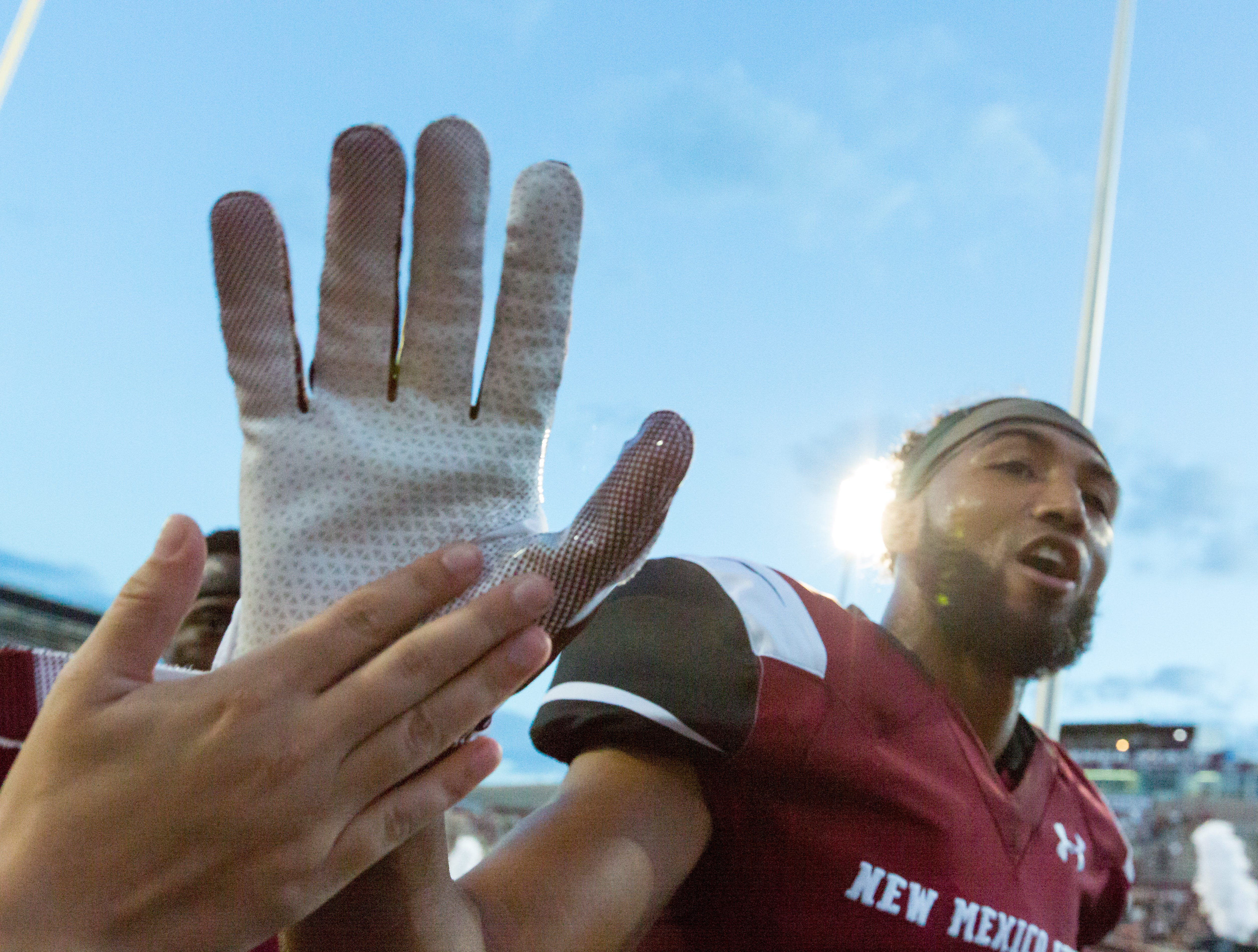 NMSU players give high fives before the game on Saturday, August 25, 2018, during the NMSU/Wyoming game at the Aggie Memorial Stadium.