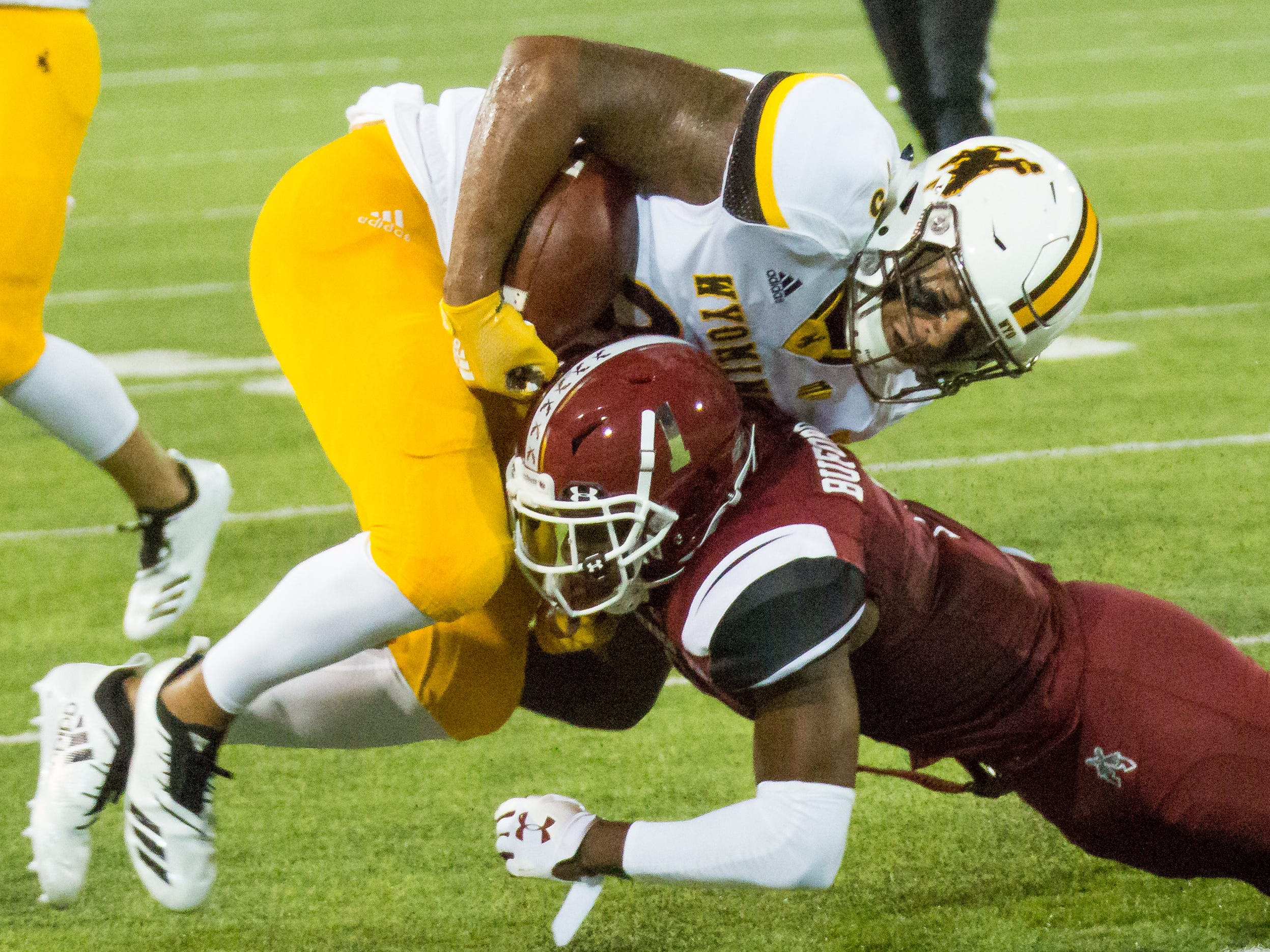 Wyoming's Tyree Mayfield holds onto the ball while NMSU defender Ray Buford Jr. on Saturday, August 25, 2018, during the NMSU/Wyoming game at the Aggie Memorial Stadium.