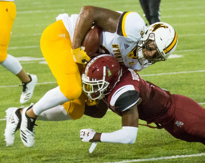 Wyoming's Tyree Mayfield holds onto the ball while NMSU defender Ray Buford Jr.  makes the tackle on August 25 at Aggie Memorial Stadium. The Aggies look for their first win of the season on Saturday at Utah State in an Arizona Bowl rematch.