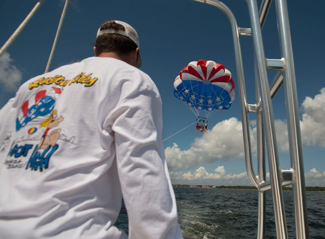 Will McCoy, 11, and Trey McCoy and Darby McCoy, 10, come in for a landing Sunday, Aug. 26, 2018 during their parasailing adventure with Radical Rides.