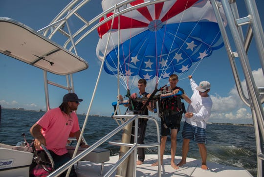 Lee and Ben McCoy get ready to take off from the Radical Rides boat Sunday, August 26, 2018 during their parasailing adventure.