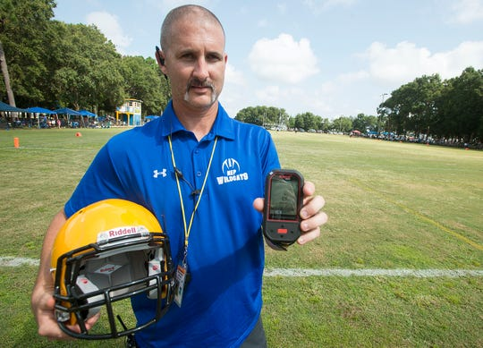 Player Safety Coordinator Michael Maddrey, holds a football helmet with an Impact Response System manufatured by Riddell. The sensor in the helmet can detect hard hits and concussion potential and send date to trainers.