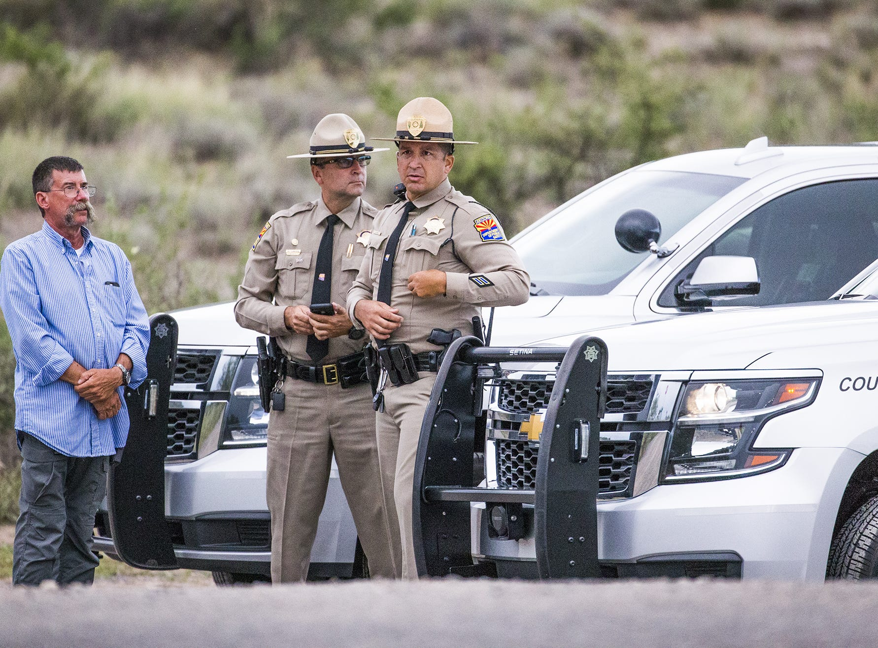 DPS troopers stand at the roadblock on Hidden Valley Road at the intersection of North Page Springs Road in Cornville on Aug. 25, 2018.  The road leads to the compound where Sen. john McCain died Saturday.