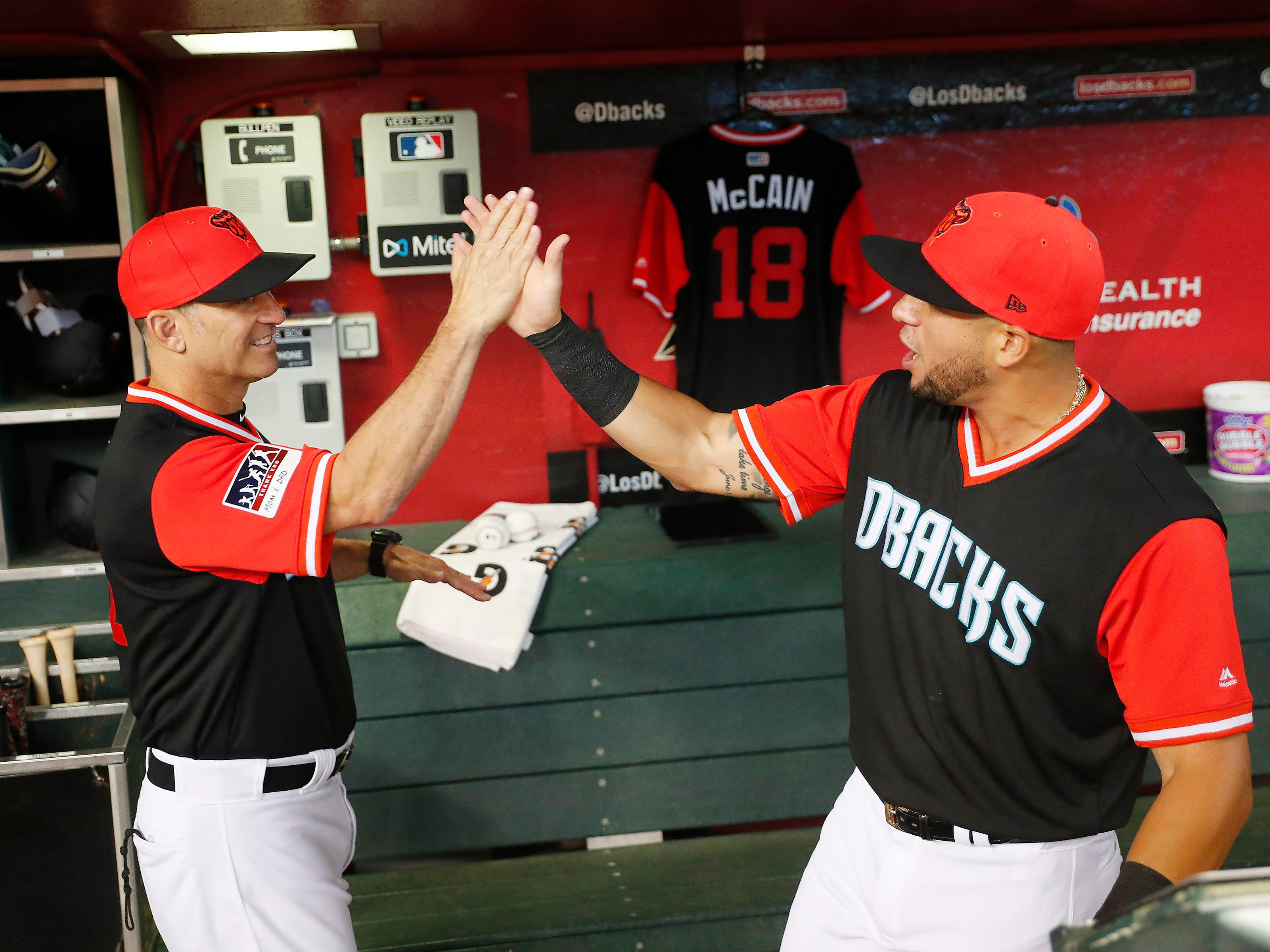 Arizona Diamondbacks manager Torey Lovullo (left0 and right fielder David Peralta slap hands in front of a jersey hanging in the dugout for Sen. John McCain before the playing against the Seattle Mariners at Chase Field in Phoenix, Ariz. August 26. 2018. The six-term Arizona senator died Saturday at age 81.