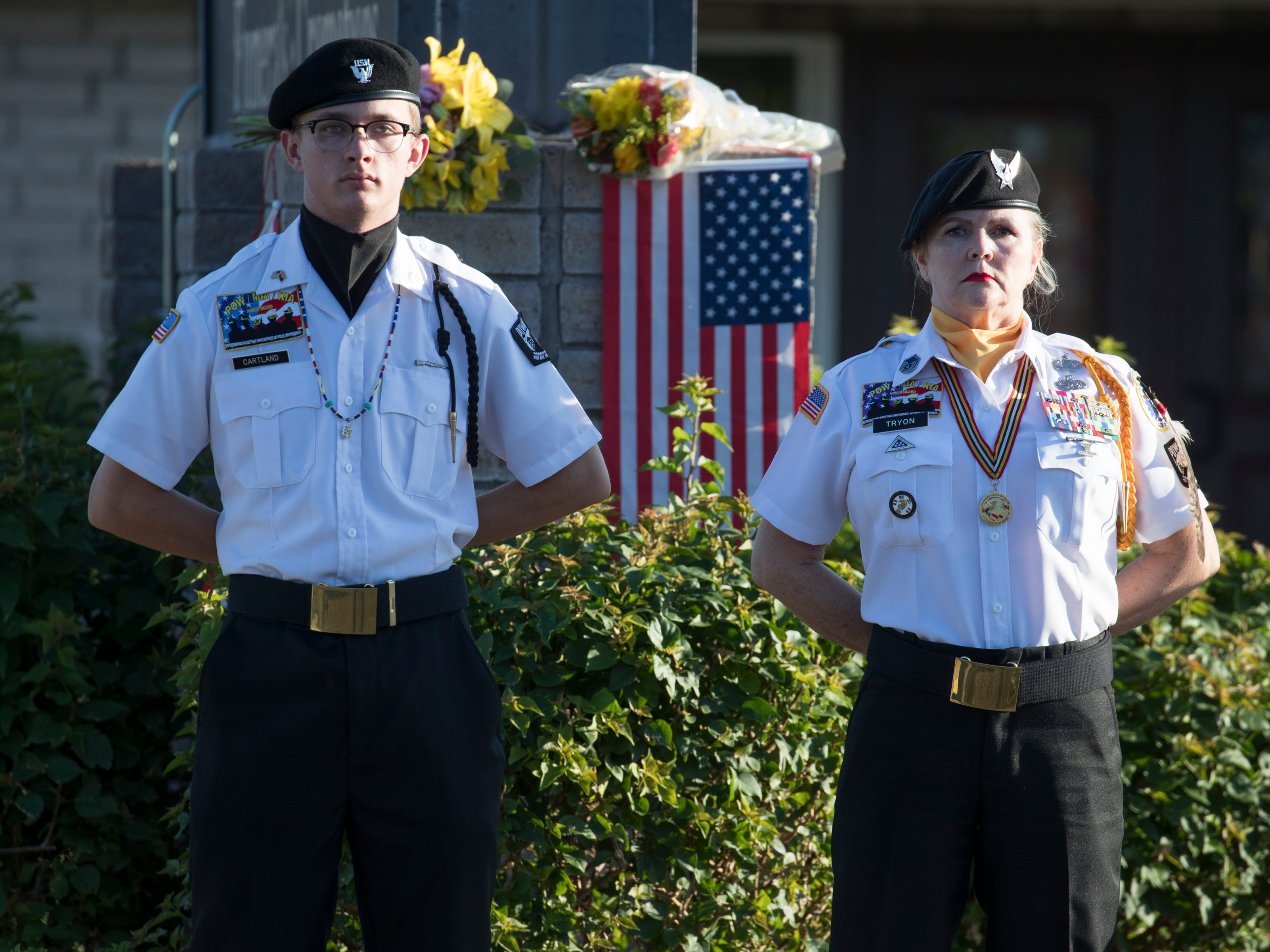 POW/MIA/KIA Honor Guard members Darlene Tryon (right) and Aaron Cartland stand watch at a makeshift memorial at the A. L. Moore Grimshaw Mortuary, Aug. 26, 2018, at 710 W. Bethany Home Road in Phoenix.