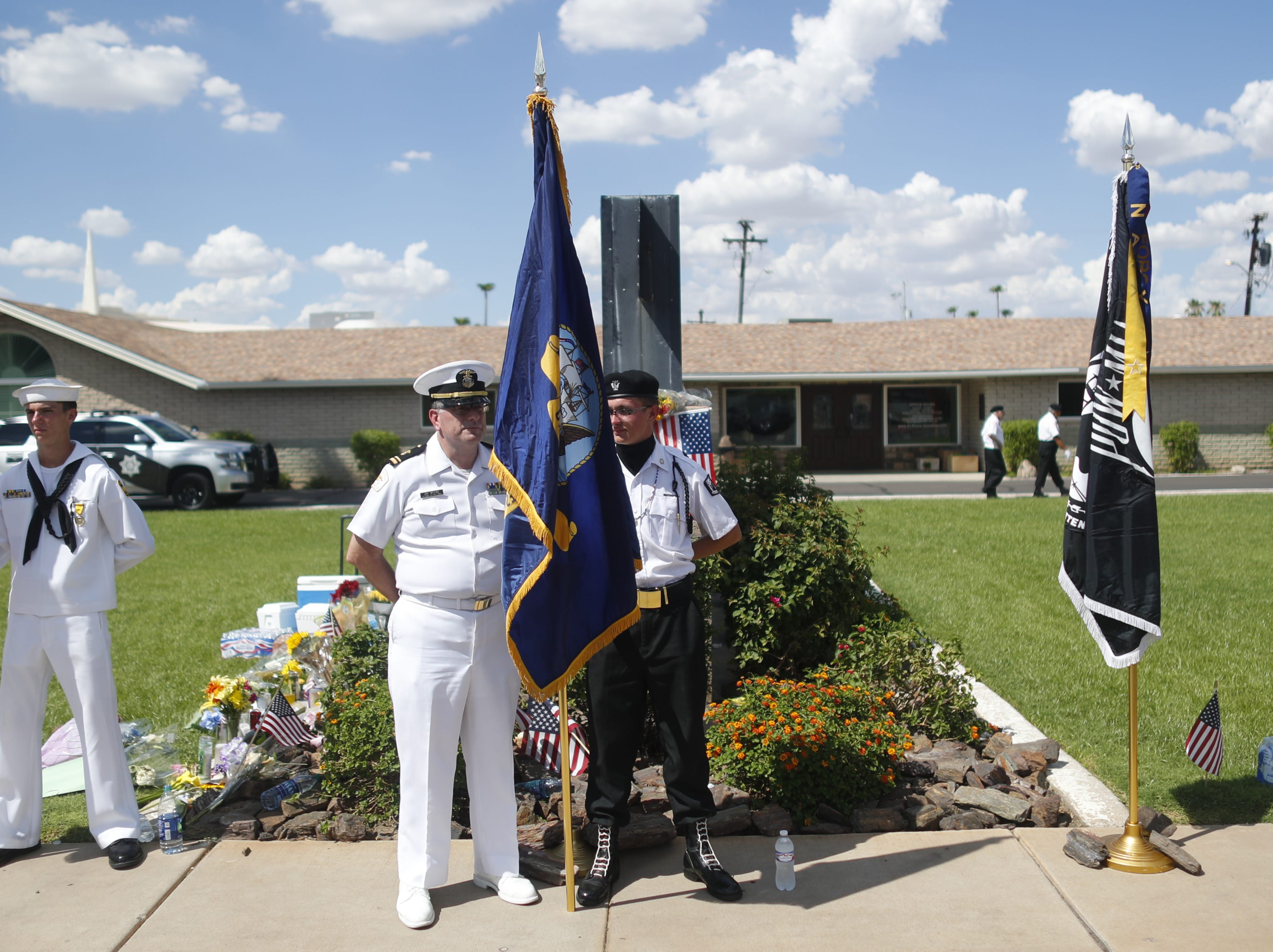 An honor guard holds its spot Aug. 26, 2018, outside A.L Moore-Grimshaw Mortuaries next to a memorial for Sen. John McCain in Phoenix.