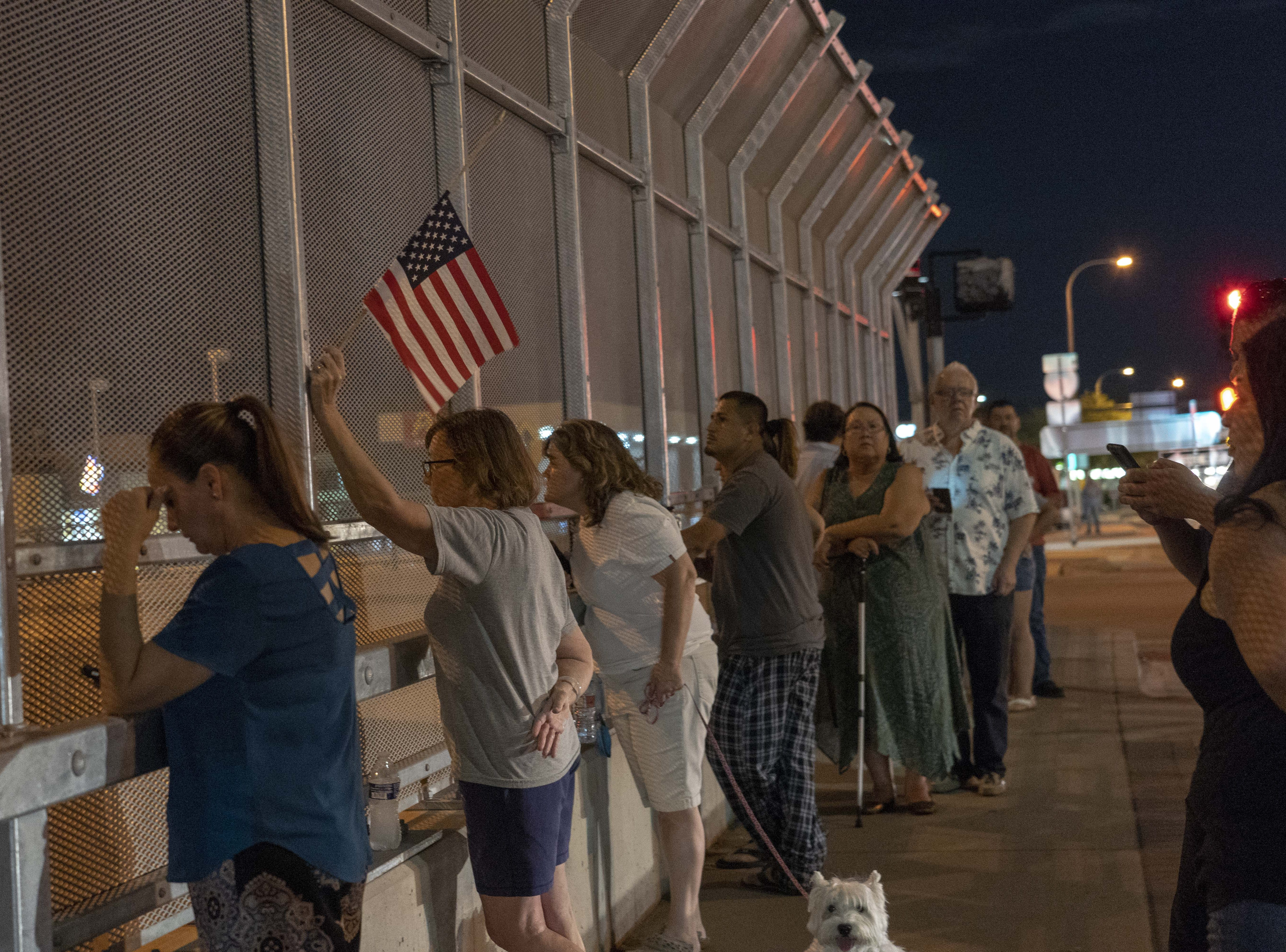 Lori Bower holds a U.S. flag while standing on an Interstate 17 overpass. Arizona residents gathered along the route a motorcade and hearse carrying Sen. John McCain's body traveled from Cornville to Phoenix.