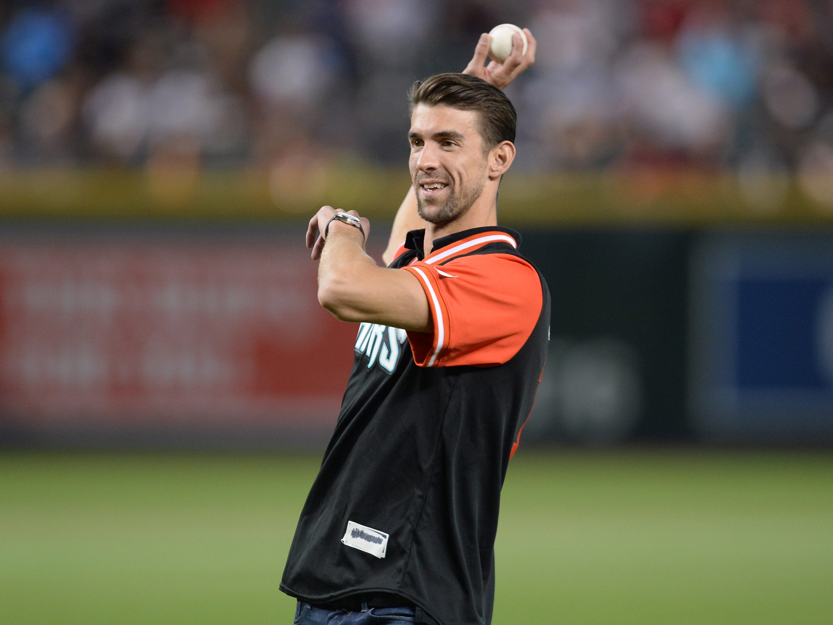 Aug 25, 2018; Phoenix, AZ, USA; Olympic gold medal swimmer Michael Phelps throws out the first pitch prior to the game between the Arizona Diamondbacks and the Seattle Mariners at Chase Field. Mandatory Credit: Joe Camporeale-USA TODAY Sports