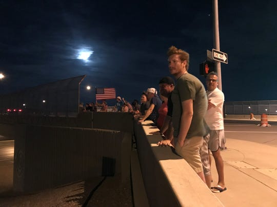 People gather at Dove Valley Road over Interstate 17 in Phoenix Saturday, Aug. 25, 2018, to watch the motorcade carrying the body of the late John McCain.