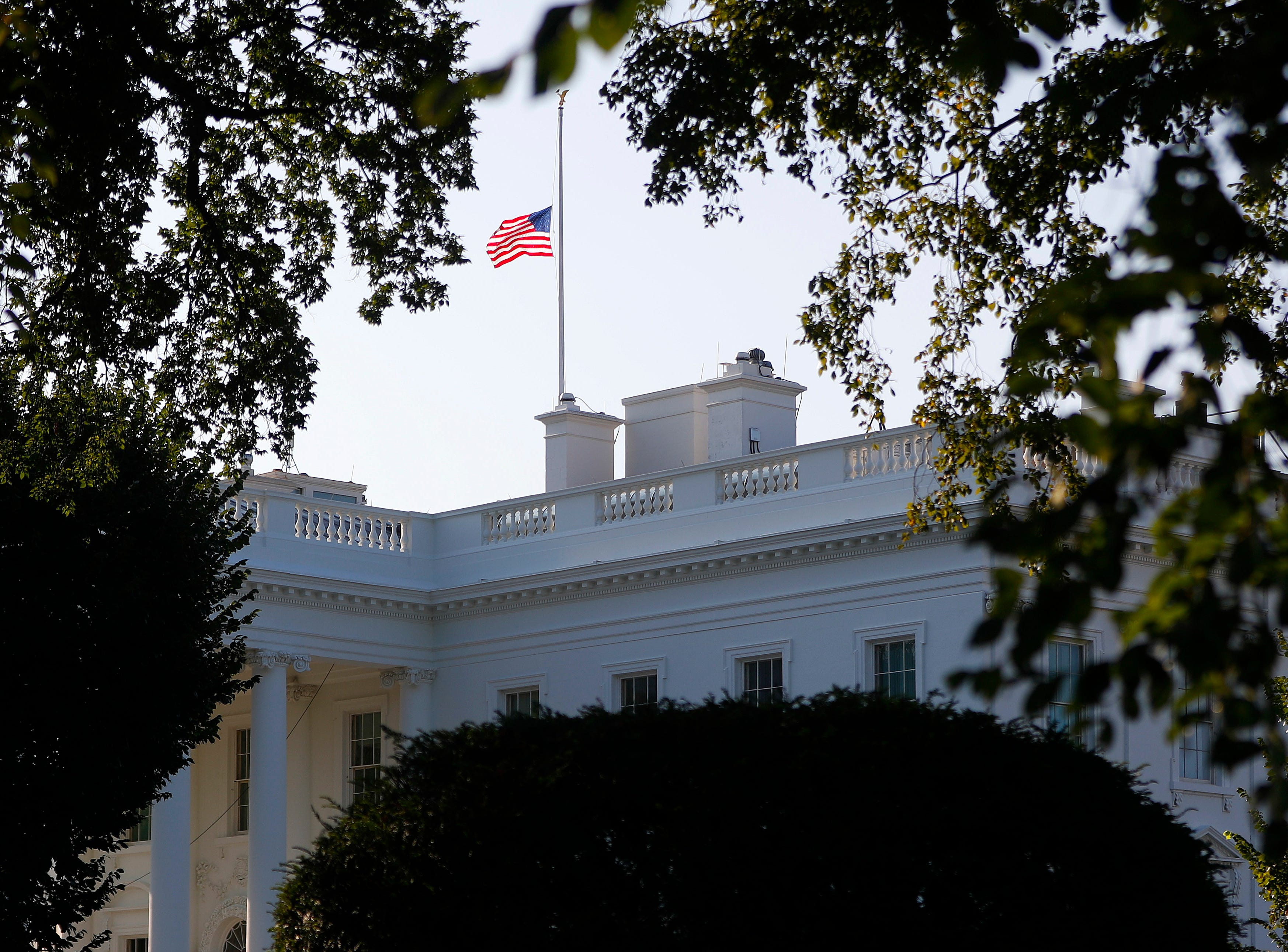 The American flag flies at half-staff above the White House in honor of Sen. John McCain, R-Ariz., Aug. 26, 2018, in Washington.