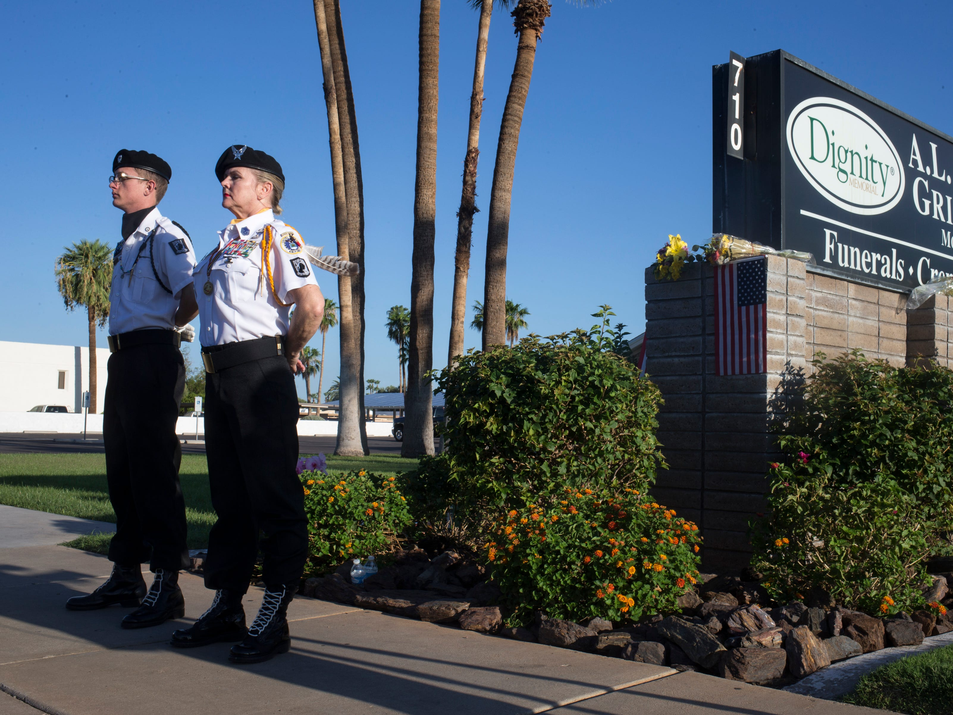 POW/MIA/KIA Honor Guard members Darlene Tryon (right) and Aaron Cartland stand watch at a makeshift memorial at the A. L. Moore Grimshaw Mortuary, Aug. 26, 2018, at 710 W. Bethany Home Road, in Phoenix.