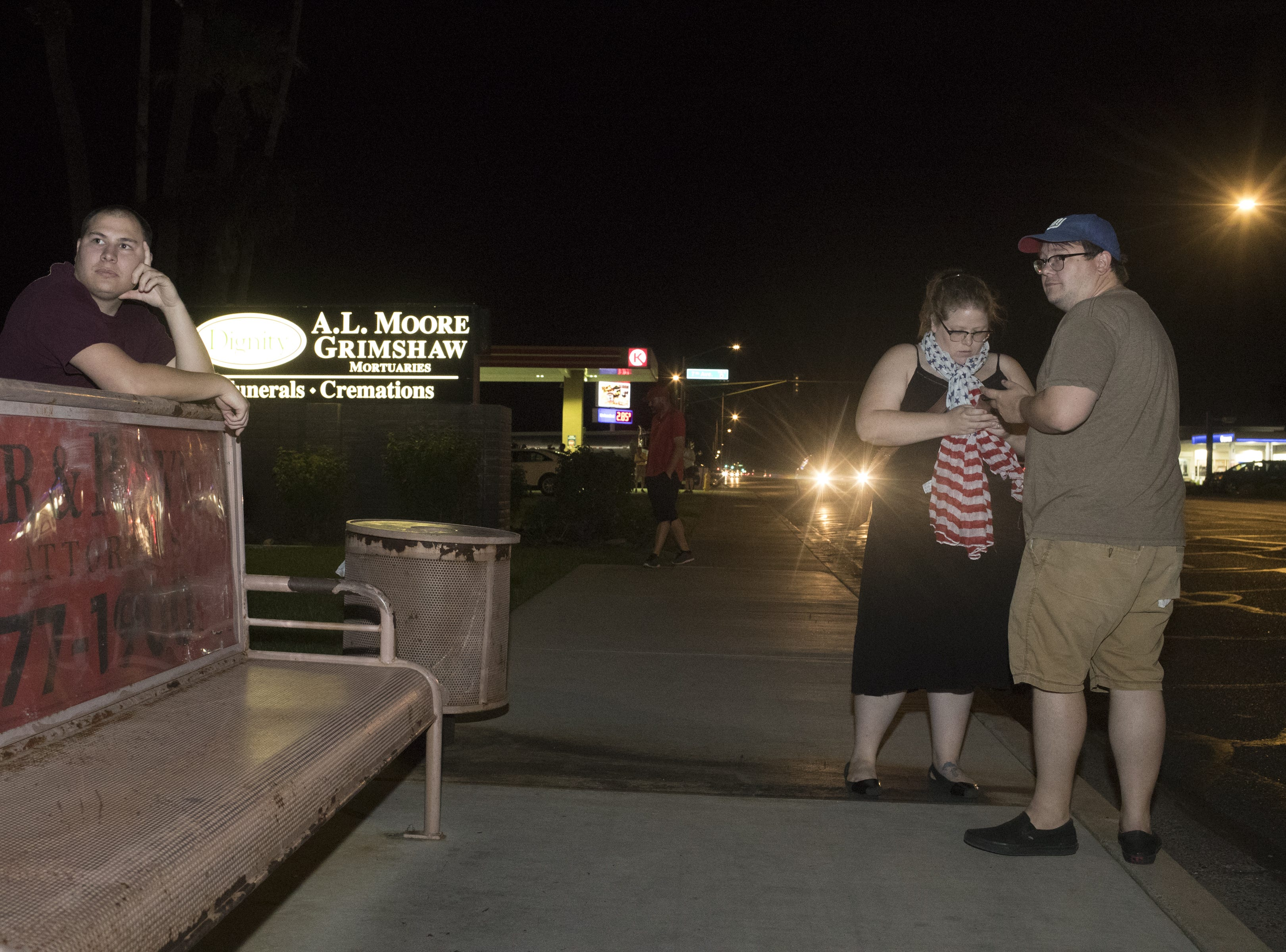 Spectators line the street while waiting for the motorcade carrying the body of Sen. John McCain arrives at the A. L. Moore Grimshaw Mortuary on Aug. 25, 2018, in Phoenix.