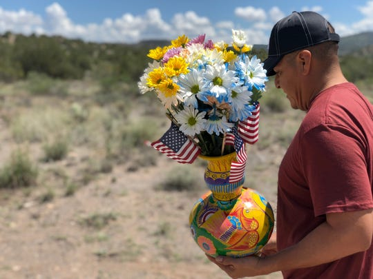 Luis Aniceto of Phoenix carries a vase with flowers to a memorial for Sen. John McCain in Cornville on Sunday, Aug. 26.