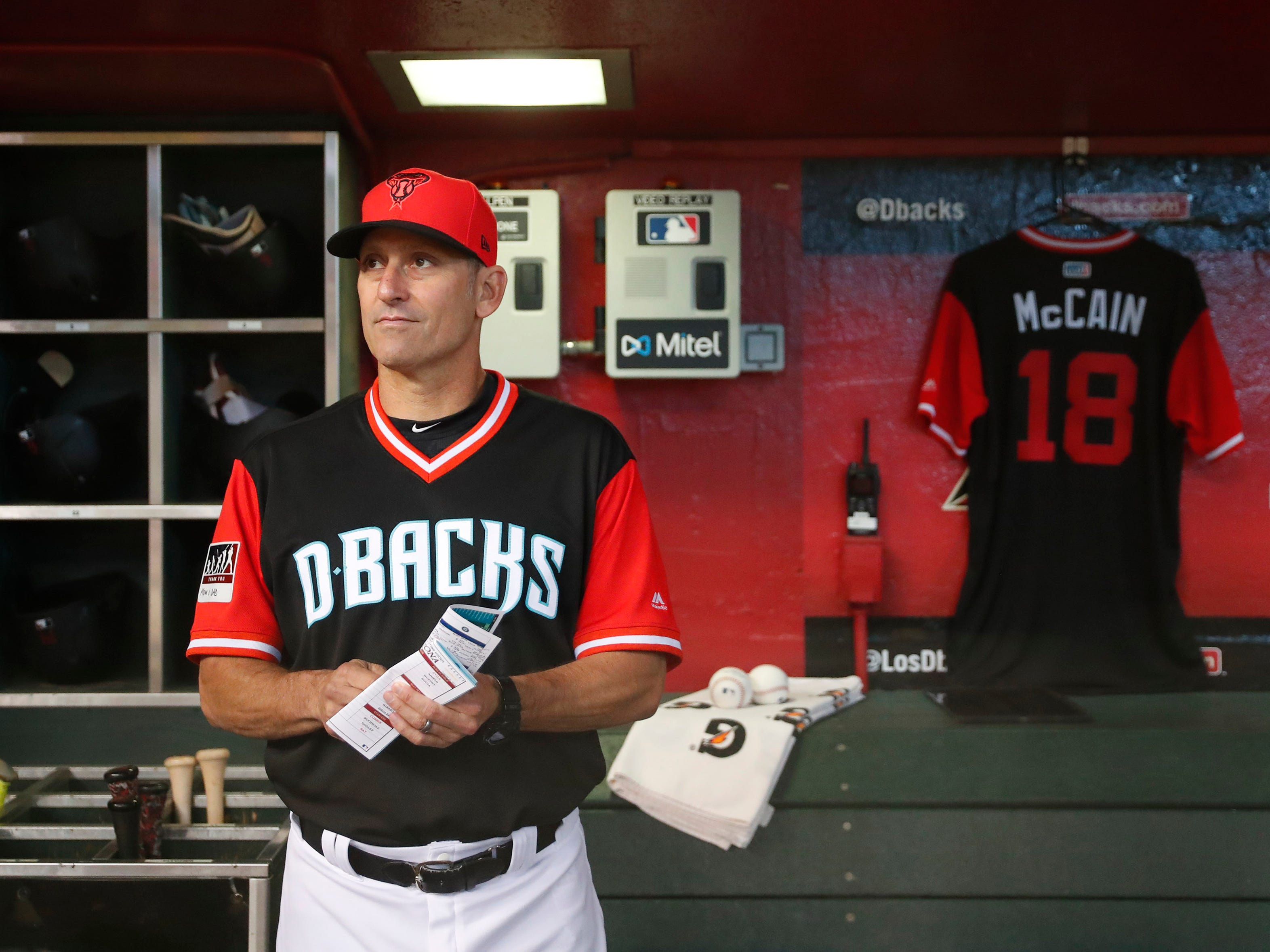 Arizona Diamondbacks manager Torey Lovullo (17) stands in the dugout next to a jersey for Sen. John McCain before playing against the Seattle Mariners at Chase Field in Phoenix, Ariz. August 26. 2018. The six-term Arizona senator died Saturday at age 81.