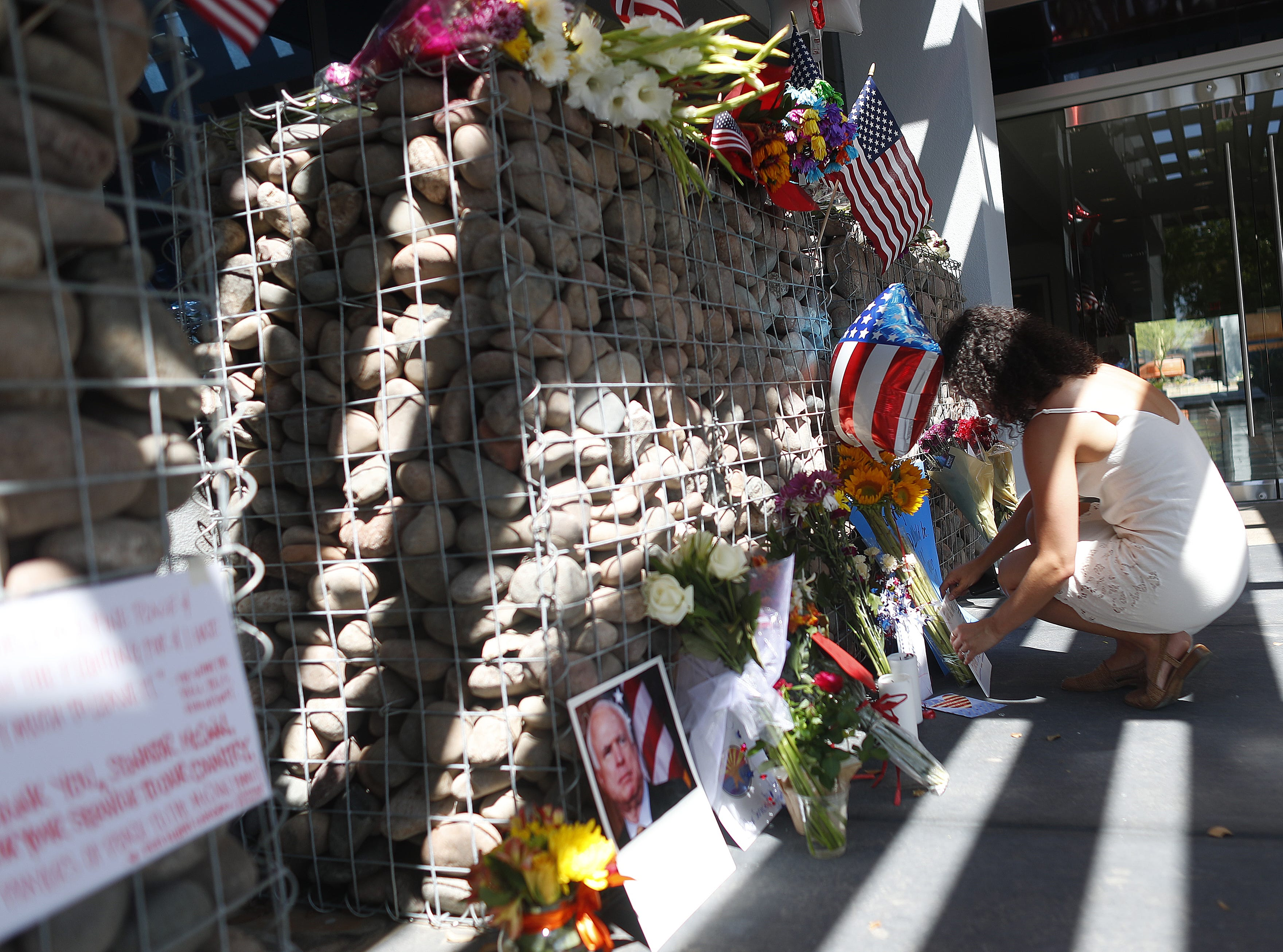 "Cass Possehl (R) lays flowers and a note Aug. 26, 2018, at a memorial outside Sen. John McCain's offices in Phoenix. Possehl began getting into politics when she was in high school in 2008 during McCain's campaign. She worked on his last campaign and loved that his philosophy of ""values and compassion over politics."""
