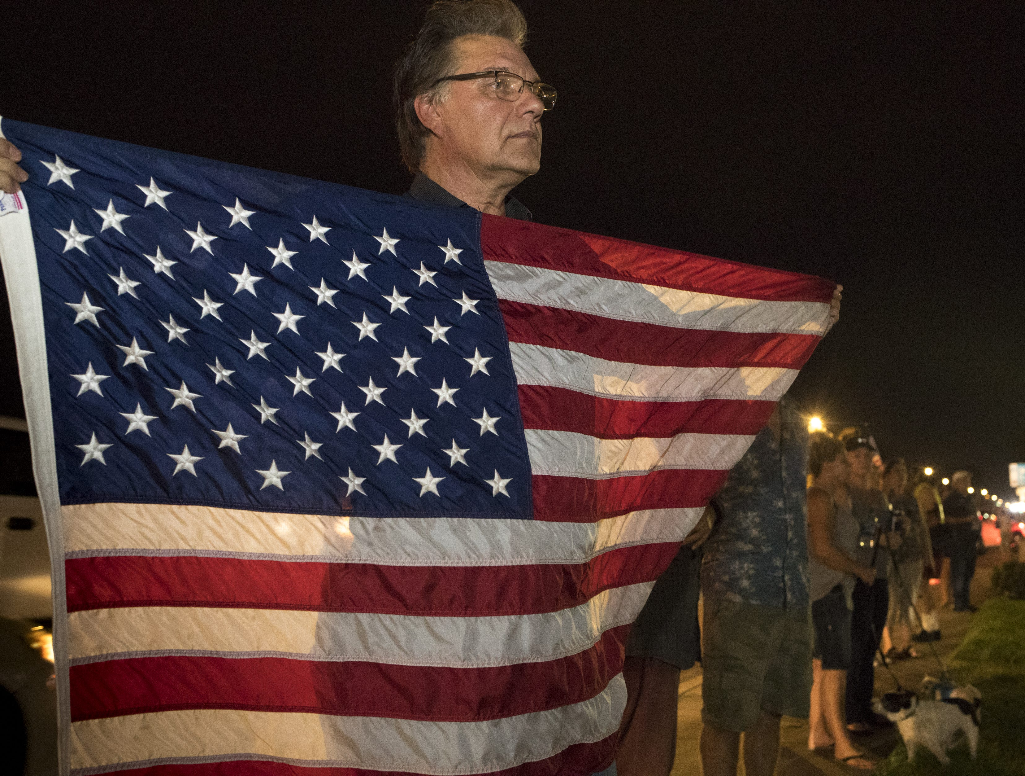Spectators, including Steve Dickman, line the street for the motorcade carrying the body of Sen. John McCain arrives at the A. L. Moore Grimshaw Mortuary, August 25, 2018, 710 W. Bethany Home Road, Phoenix, Arizona.