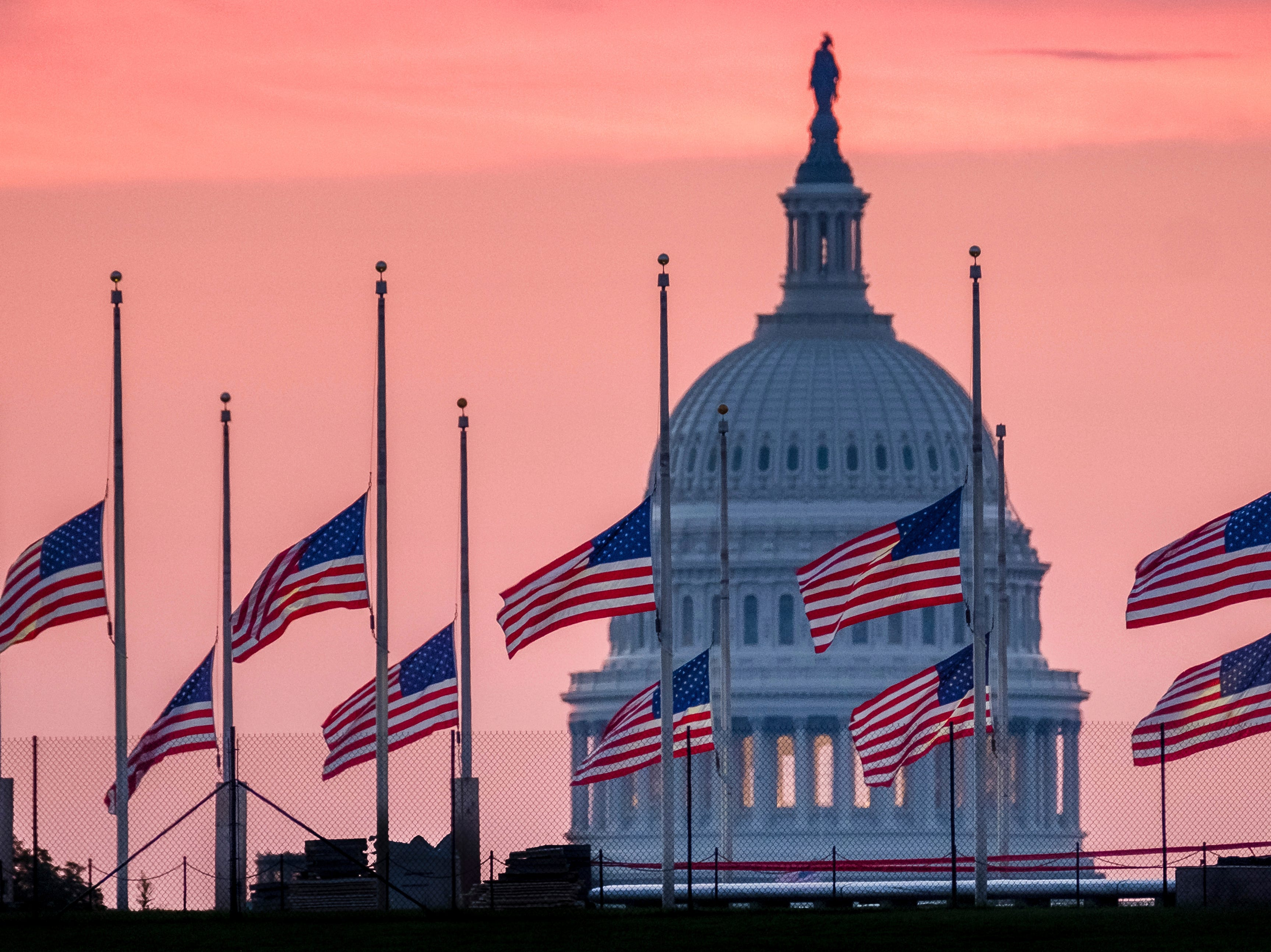 Flags flying at half-staff in honor of Sen. John McCain, R-Ariz., frame the U.S. Capital at daybreak in Washington on Aug. 26, 2018. McCain, 81, died at his ranch in Arizona after a yearlong battle with brain cancer.