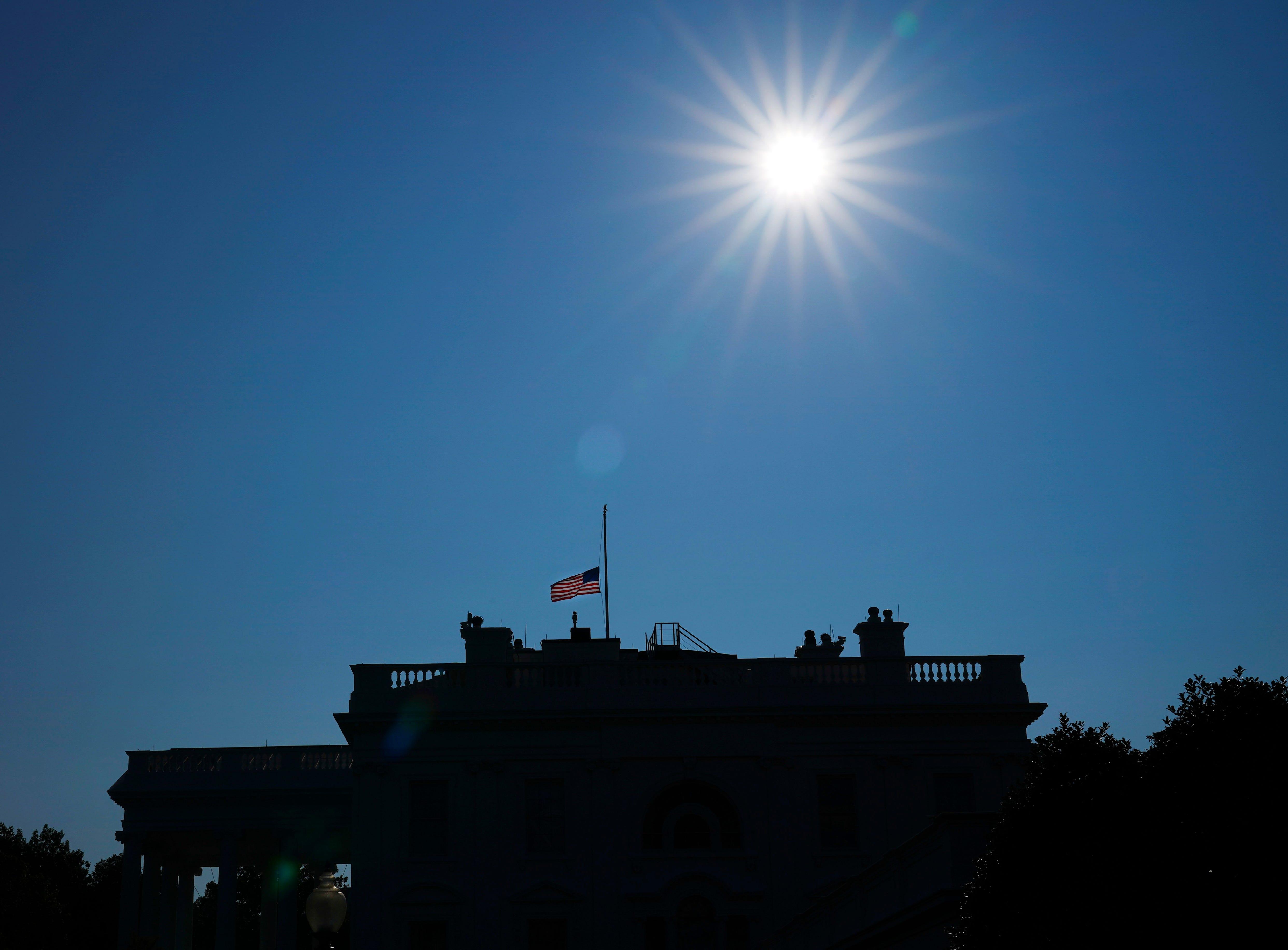 The American flag flies at half-staff above the White House in honor of Sen. John McCain, R-Ariz., Aug. 26, 2018, in Washington.