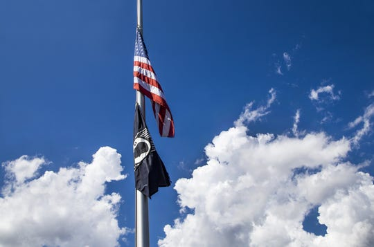 An American flag and a POW flag fly at half-staff outside the American Legion Hall, Post 25 in Cottonwood, Arizona, Sunday morning, Aug. 26, 2018.  McCain died Saturday at his home and is being mourned by millions around the world.