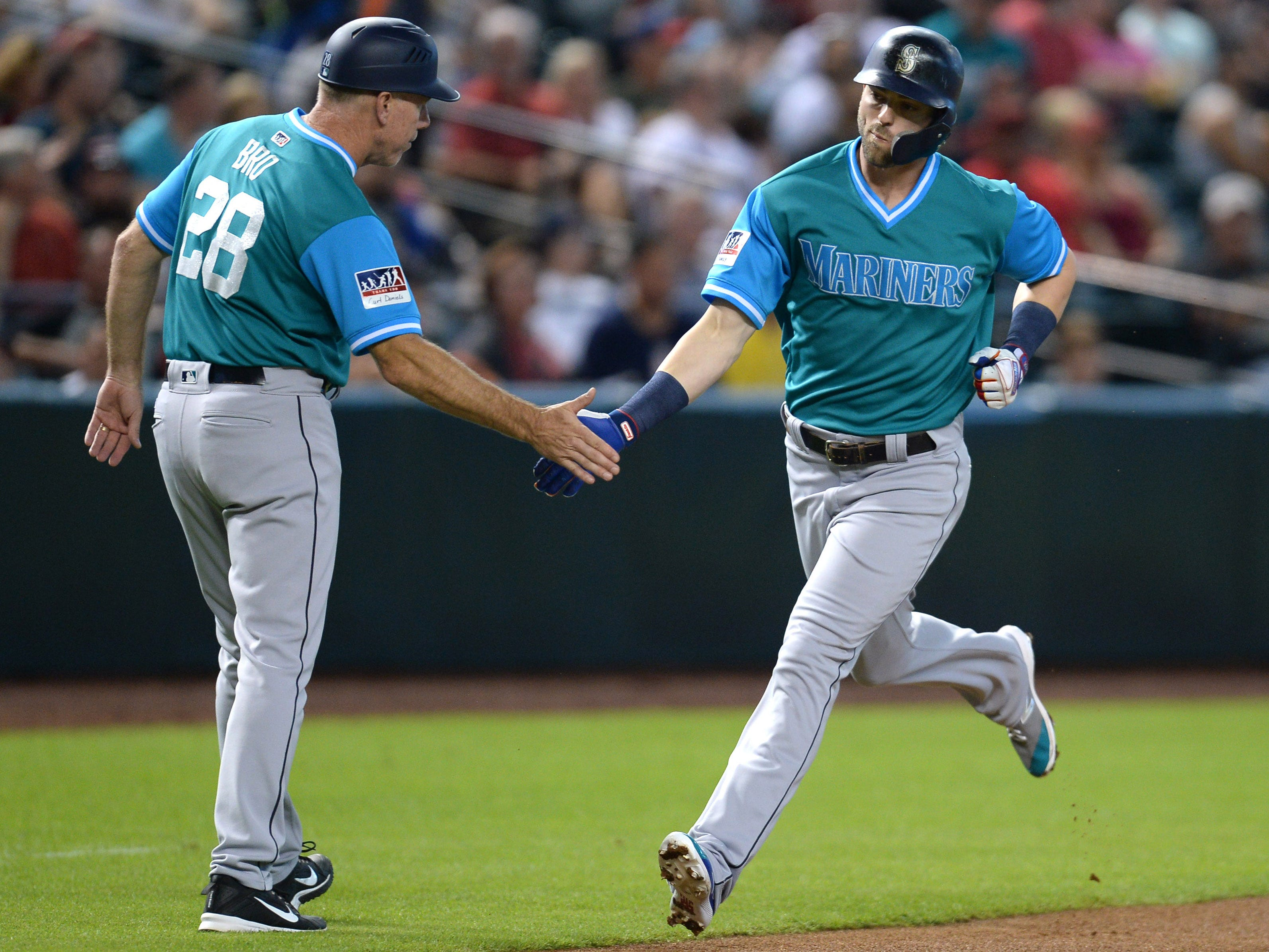 Aug 25, 2018; Phoenix, AZ, USA; Seattle Mariners right fielder Mitch Haniger (17) slaps hands with Seattle Mariners third base coach Scott Brosius (28) after hitting a solo home run against the Arizona Diamondbacks during the first inning at Chase Field. Mandatory Credit: Joe Camporeale-USA TODAY Sports
