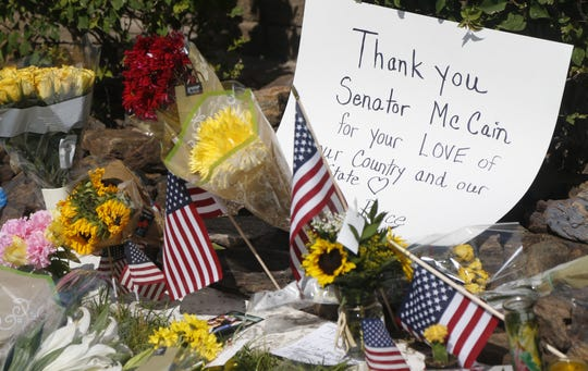 Flags, flowers and notes are left outside A.L. Moore-Grimshaw Mortuaries on Aug. 26, 2018, honoring the late Sen. John McCain in Phoenix.