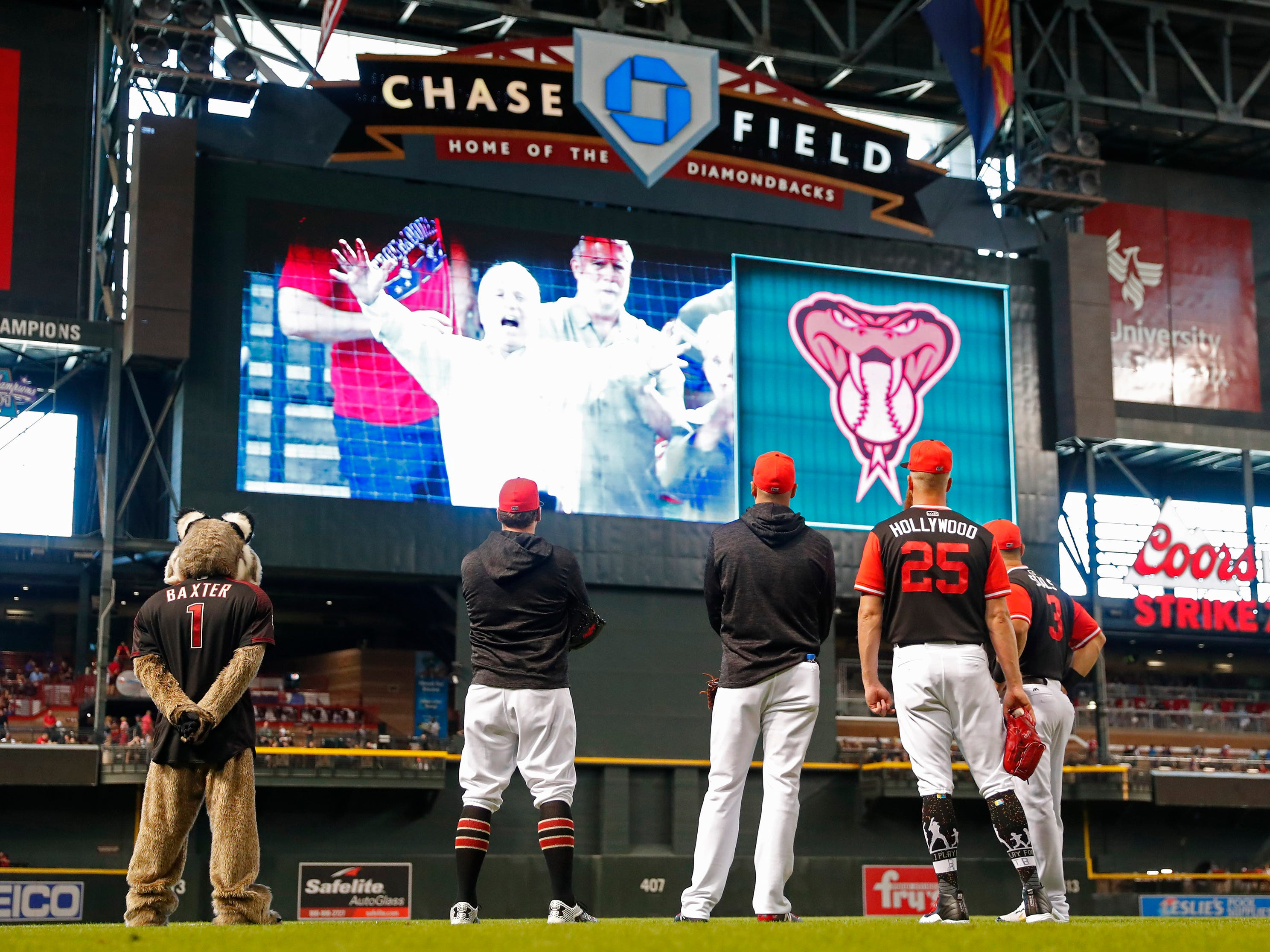 Arizona Diamondbacks players watch a video tribute to Sen. John McCain before playing against the Seattle Mariners at Chase Field in Phoenix, Ariz. August 26. 2018. The six-term Arizona senator died Saturday at age 81.