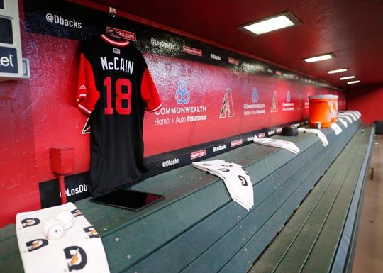 A jersey for Sen. John McCain hangs in the Diamondbacks dugout before Sunday's game.