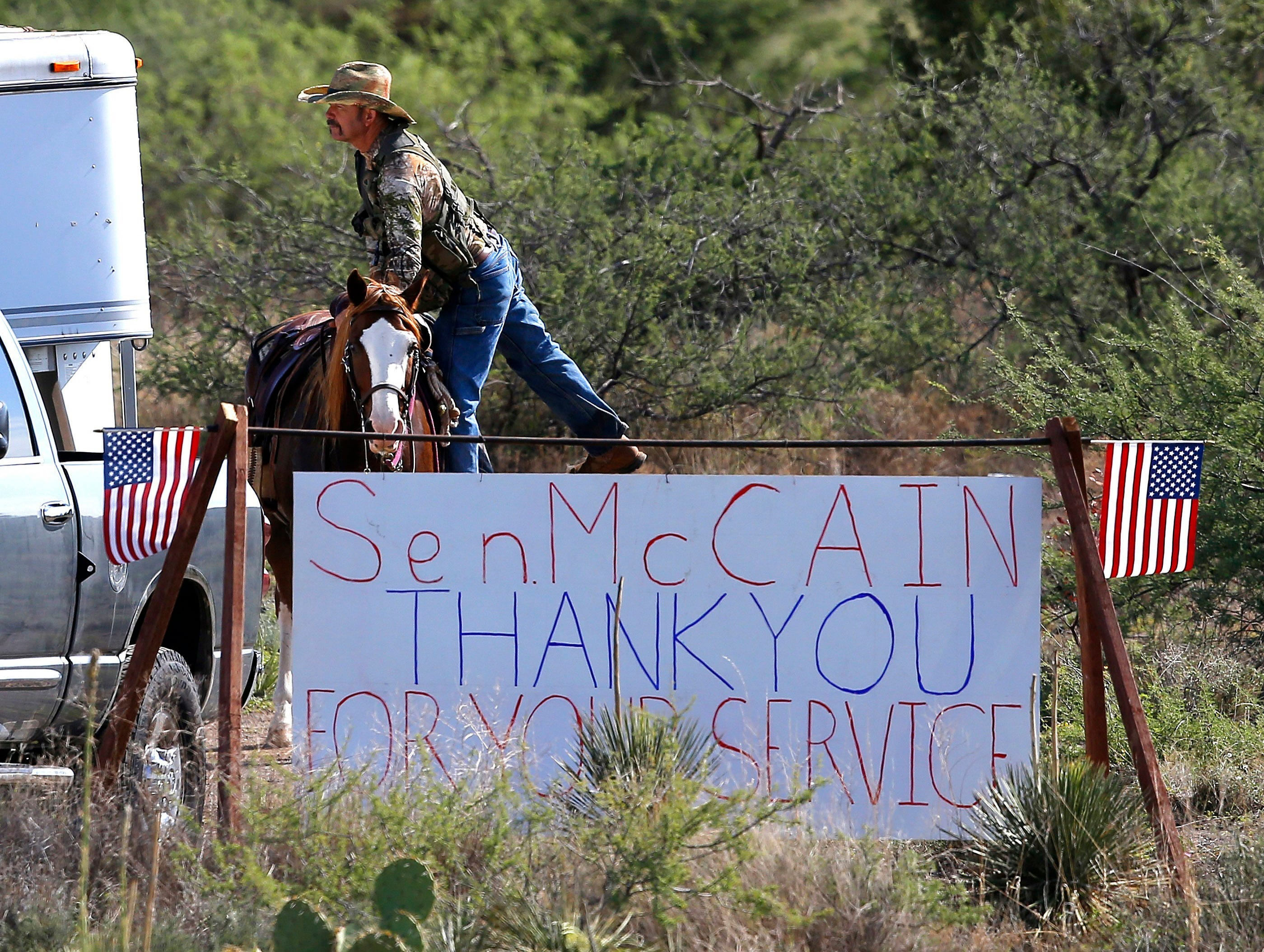 A rancher gets off his horse at the entrance to the McCain compound on Aug. 25, 2018, in Cornville.